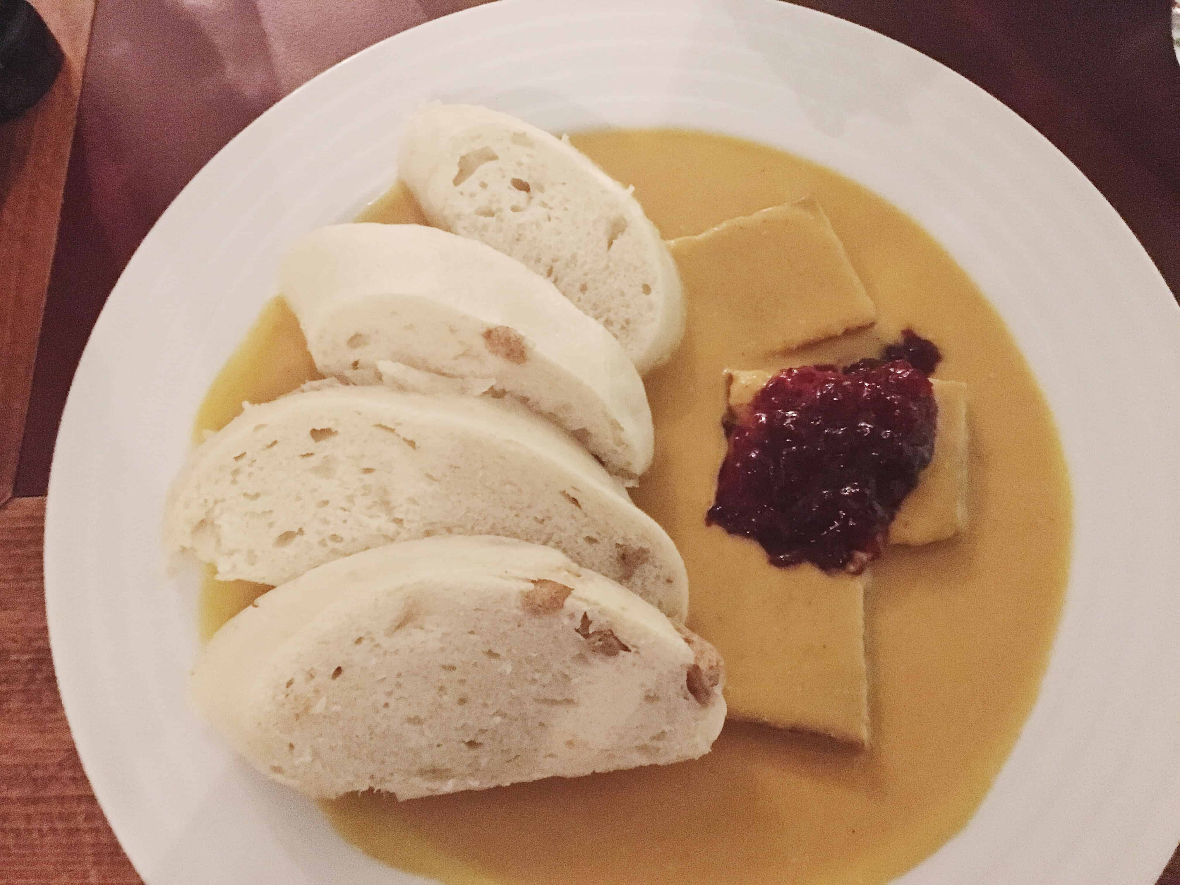 Svíčková is a delicious traditional dish from the Czech Republic, made with beef (tempeh if vegetarian), dumplings, cranberries, whipped cream, and a cream sauce