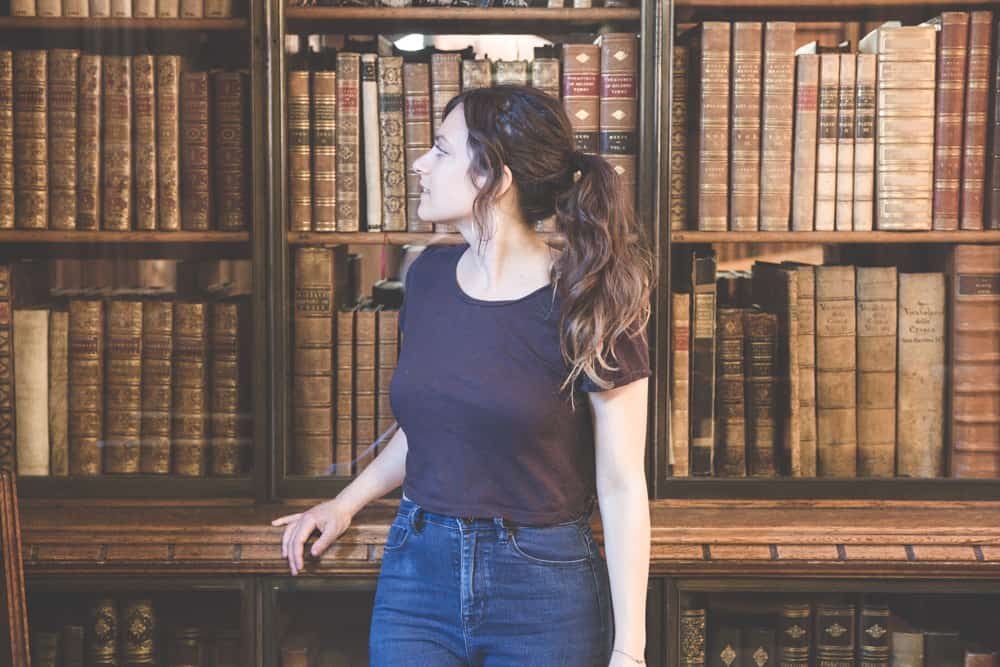 Kelsey in front of old books in the John Rylands Library in Manchester, England