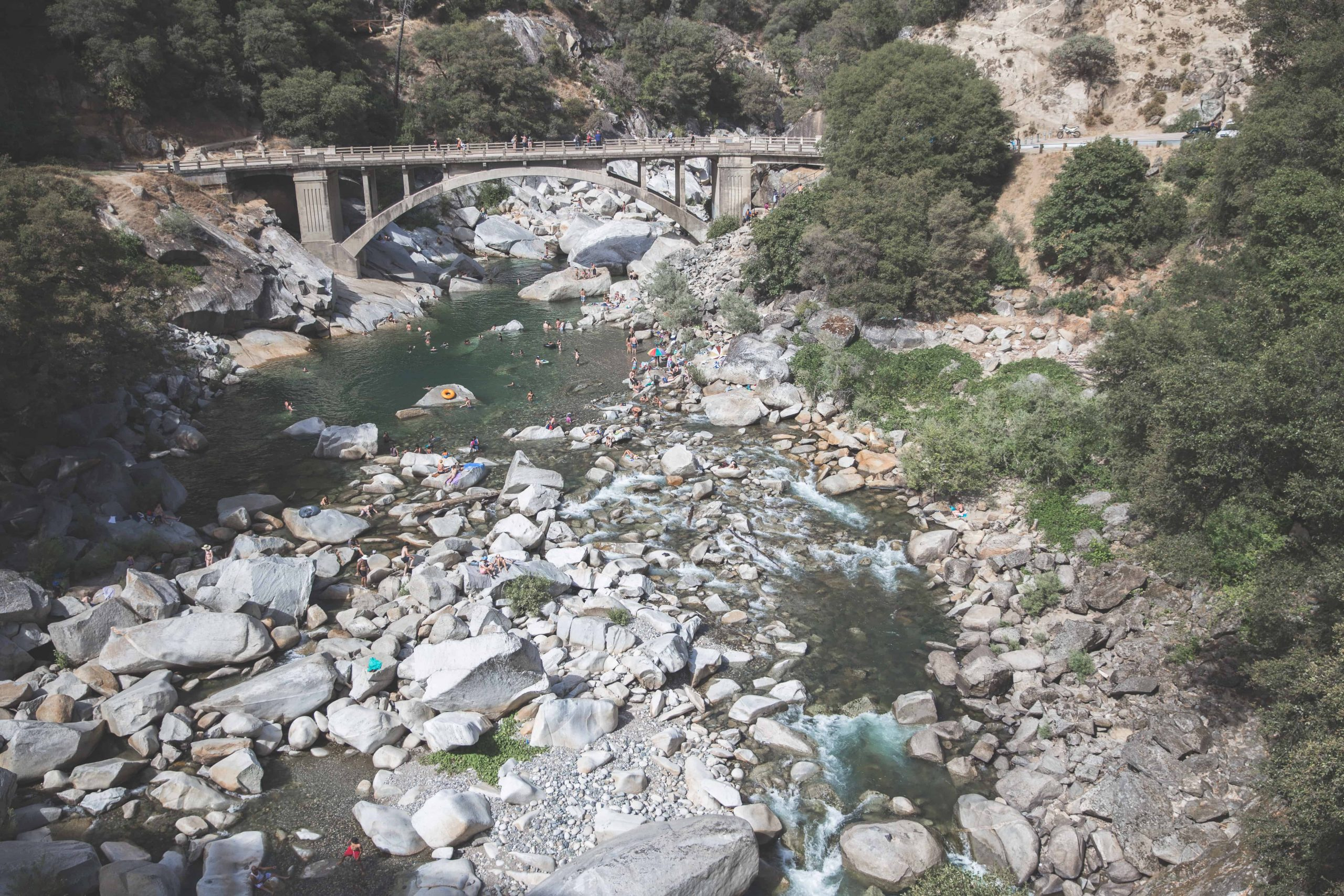 The Yuba River in California flows through lots of rocks and under a bridge. There are people swimming in it, surrounded by trees.