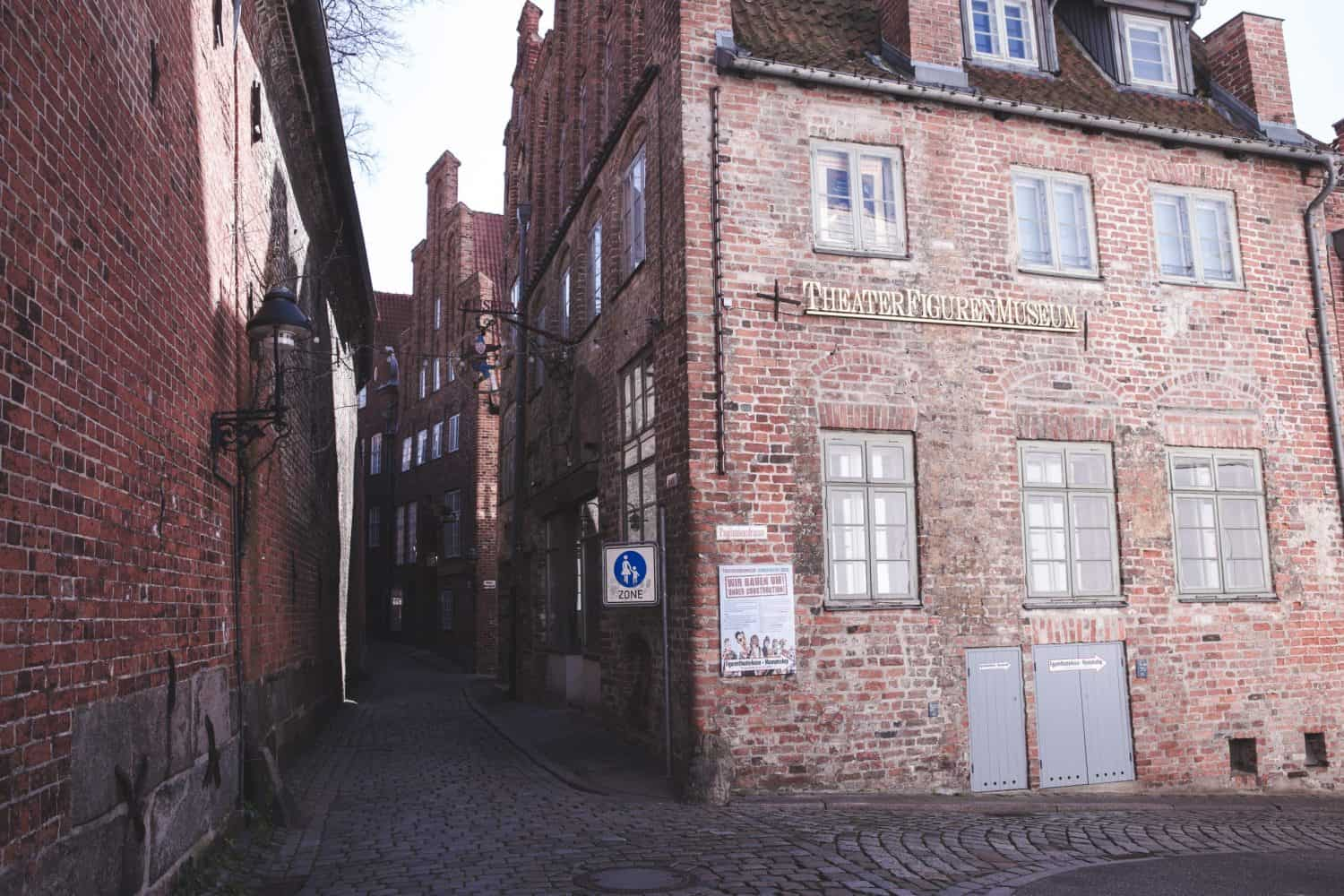 Theater Museum in Lübeck, Germany on a pretty cobblestone street surrounded by red brick buildings.