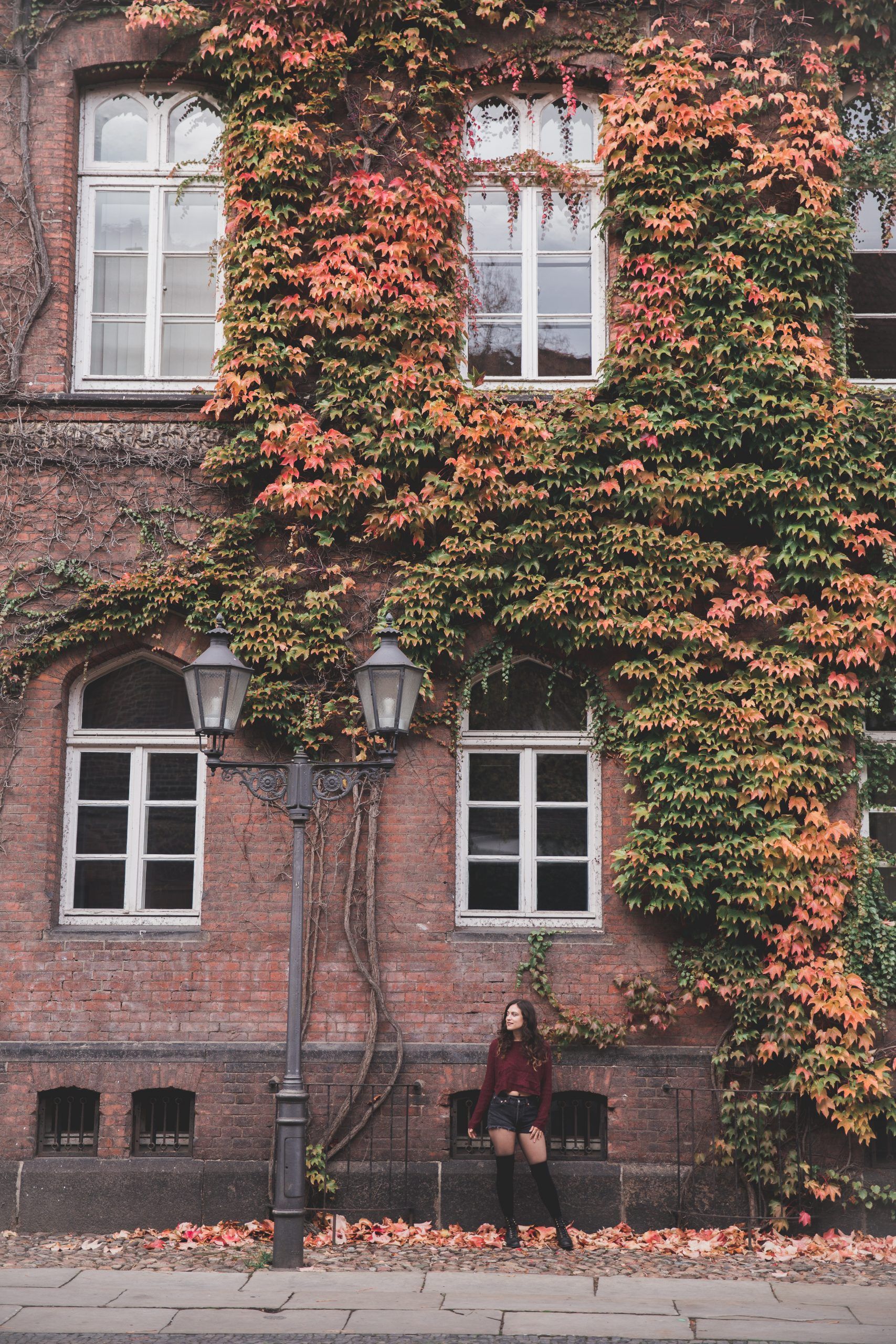 Kelsey in front of a brick building covered in red, yellow, orange, and green ivy in Lüneburg, a day trip from Hamburg, Germany