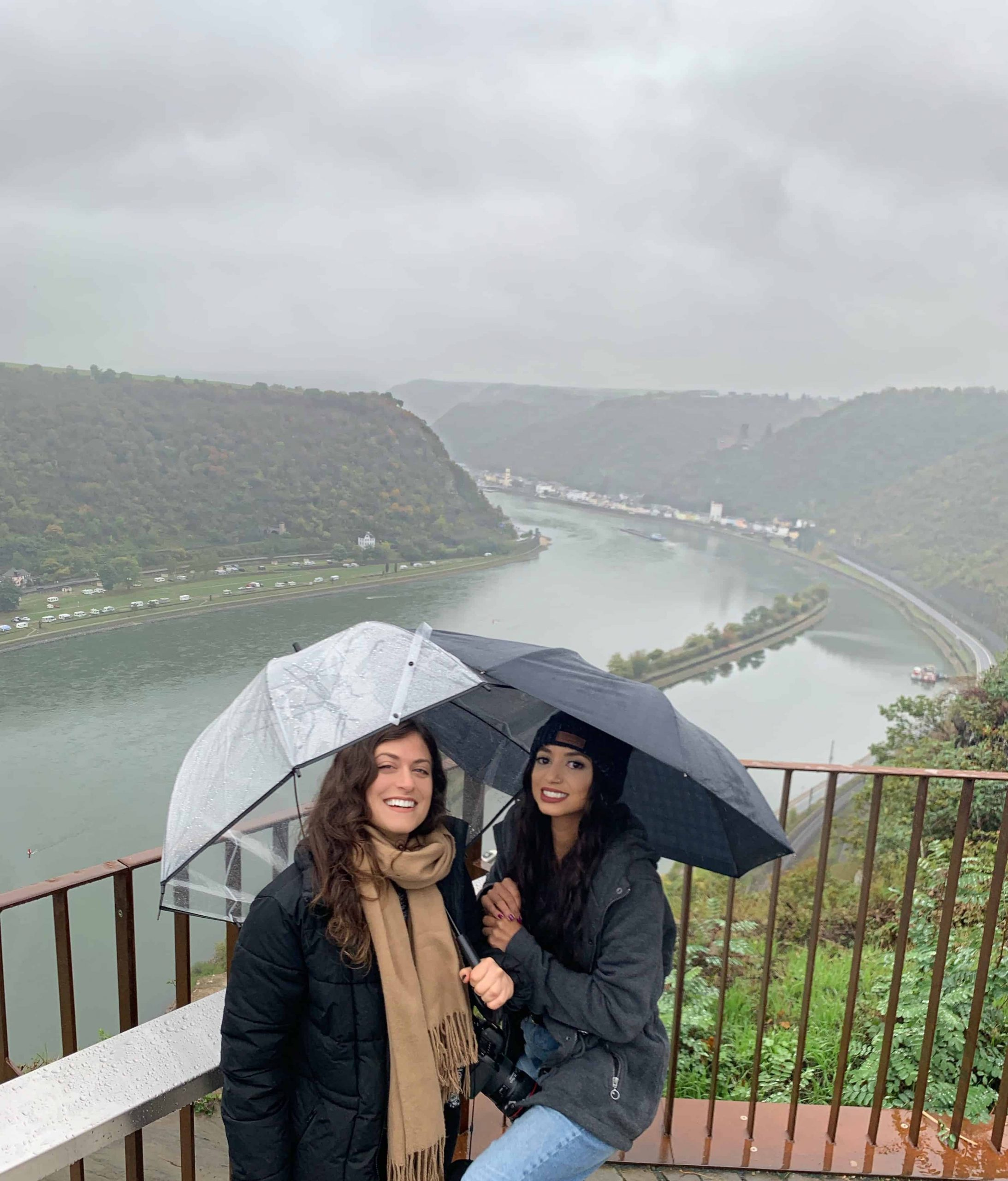 Kelsey and her friend with umbrellas at an overlook over the Mosel River in Germany