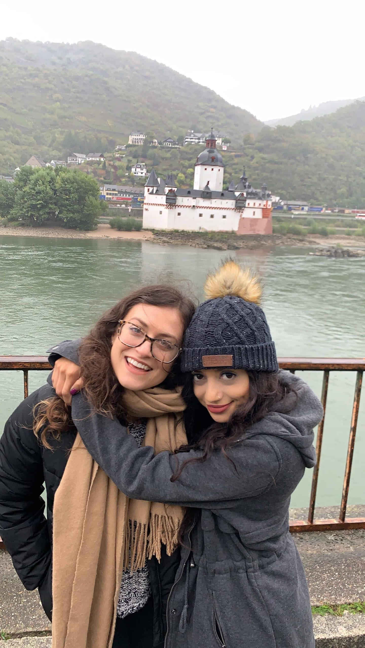 Kelsey and her friend hugging with the Mosel River and a castle in the background in Germany