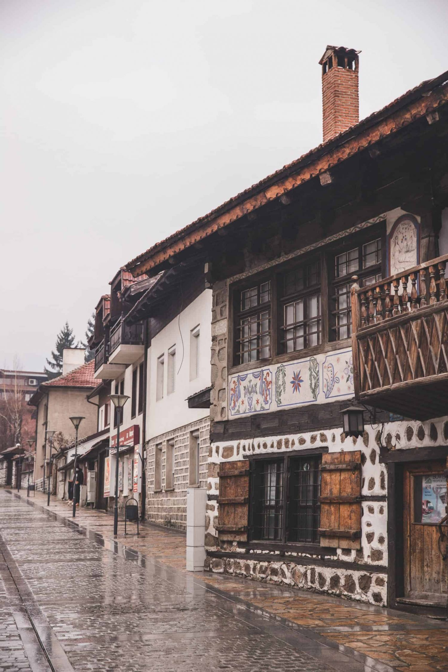 The road up Pirin Street in Bansko's Old Town has cobblestone streets and old stone and traditional Bulgarian buildings.