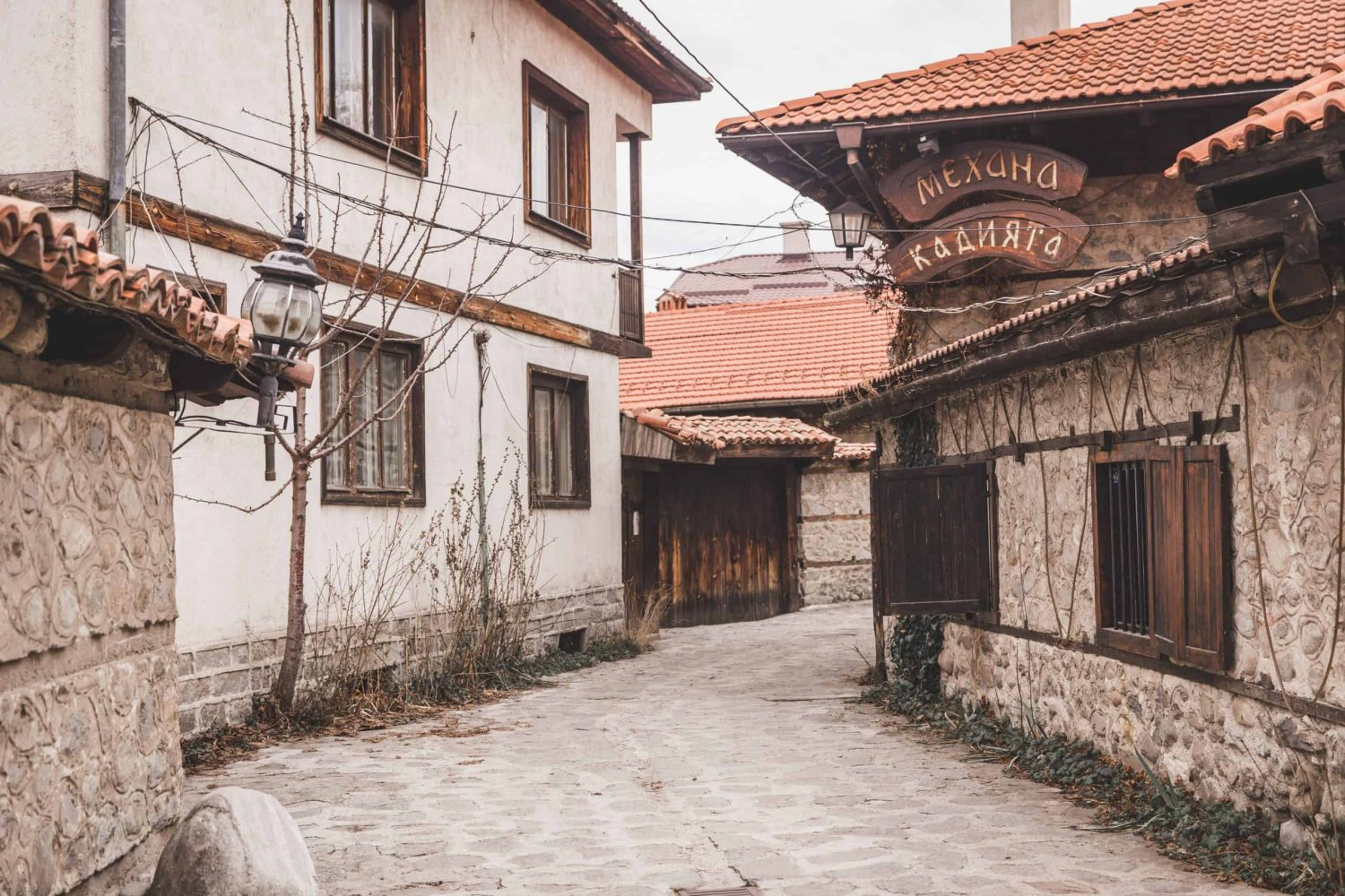 Cobblestone street and stone walls on old tiled rooftop houses in Bansko, Bulgaria's Old Town.