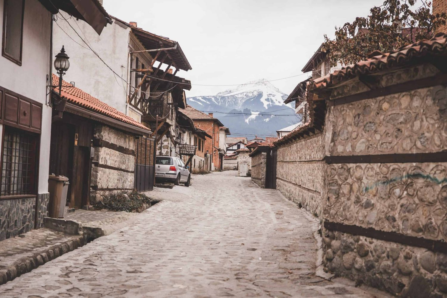 A cobblestone street with stone walls and houses with a view of snow covered mountains in Bansko, Bulgaria's Old Town.