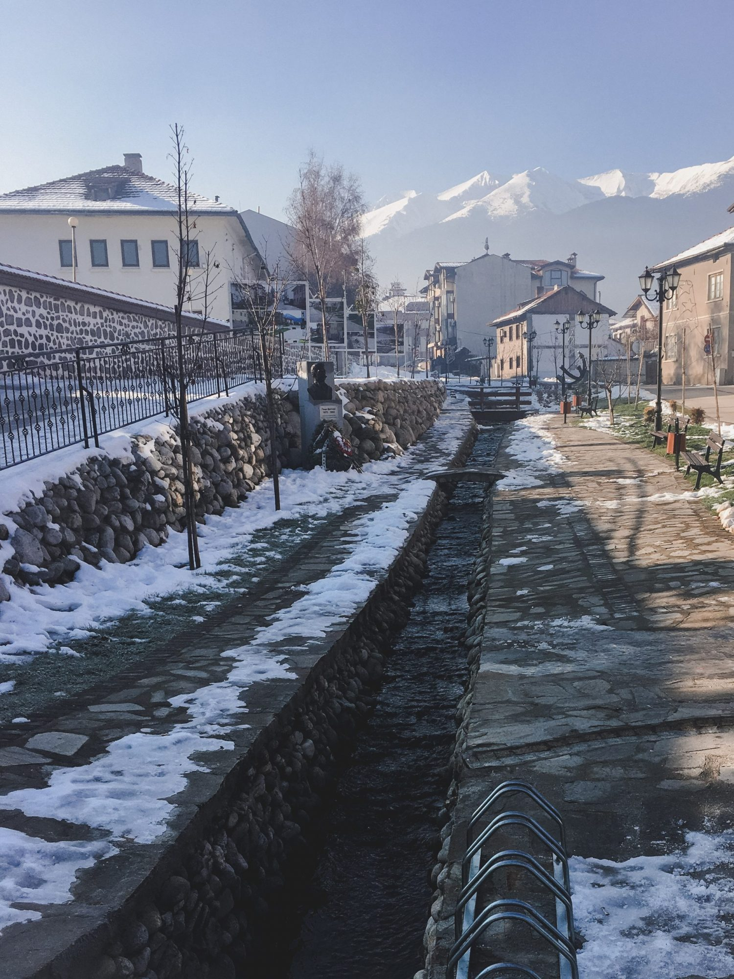 "The street ul ""Gotse Delchev"" in Bansko, Bulgaria in winter. It has a stream running through it and views of snow-covered mountains."