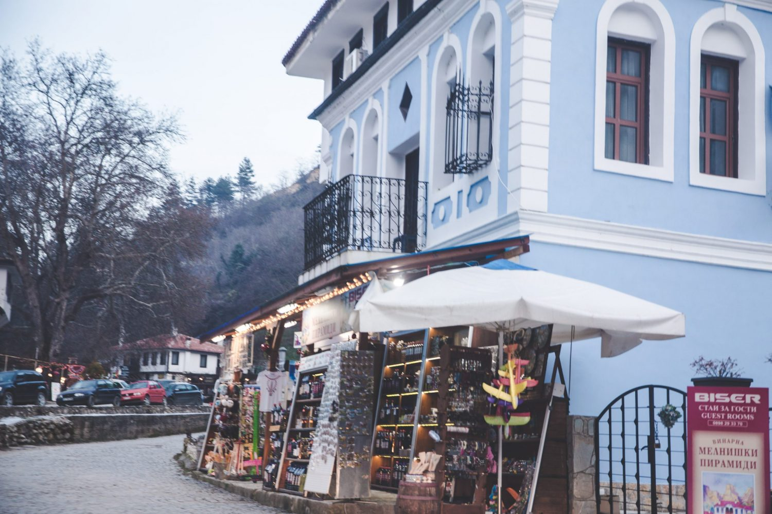 A light blue building on the main street in Melnik, Bulgaria that sells various goods.