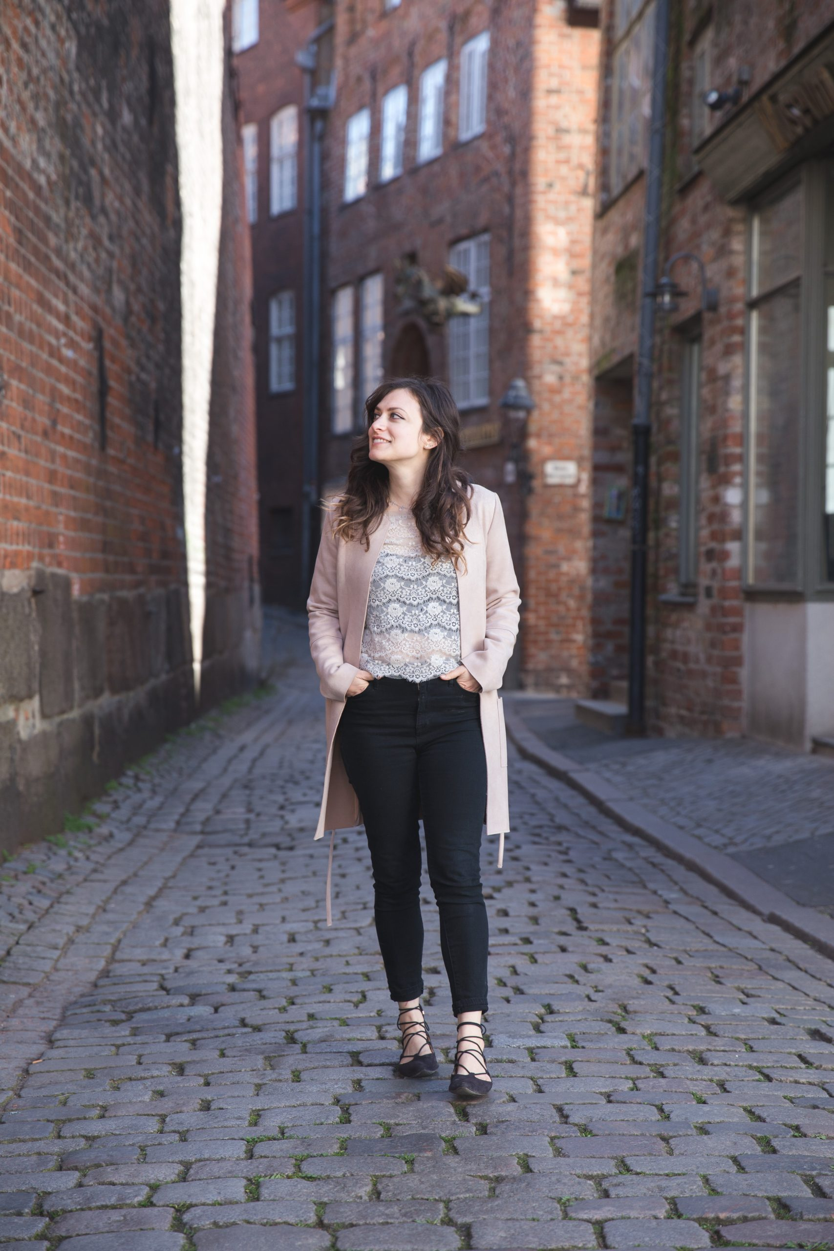 Kelsey Alone in Lübeck, Germany on a cobblestone street surrounded by brick buildings