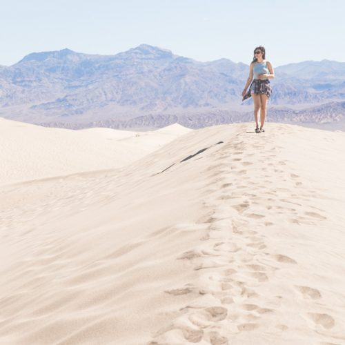 Kelsey, a digital nomad, walking on sand dunes in Death Valley with mountains behind her