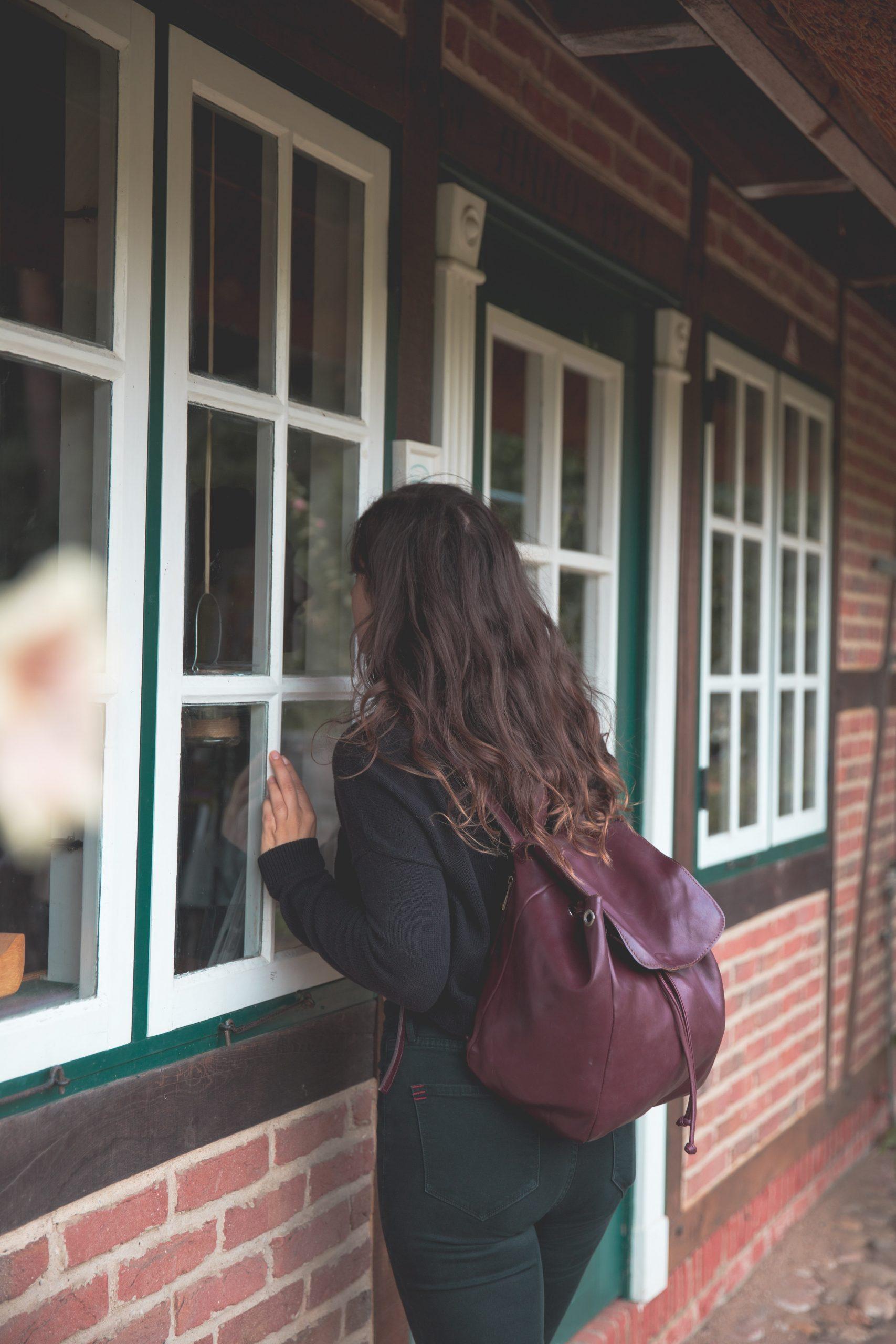 Kelsey Looking Through a Window of a brick building in the Loki Schmidt Botanical Gardens in Hamburg, Germany