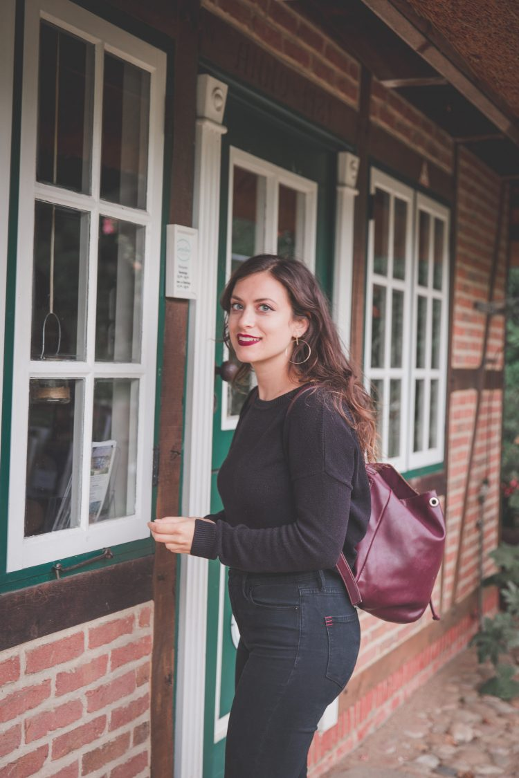Kelsey, a digital nomad, staring at the camera with a brick house behind her