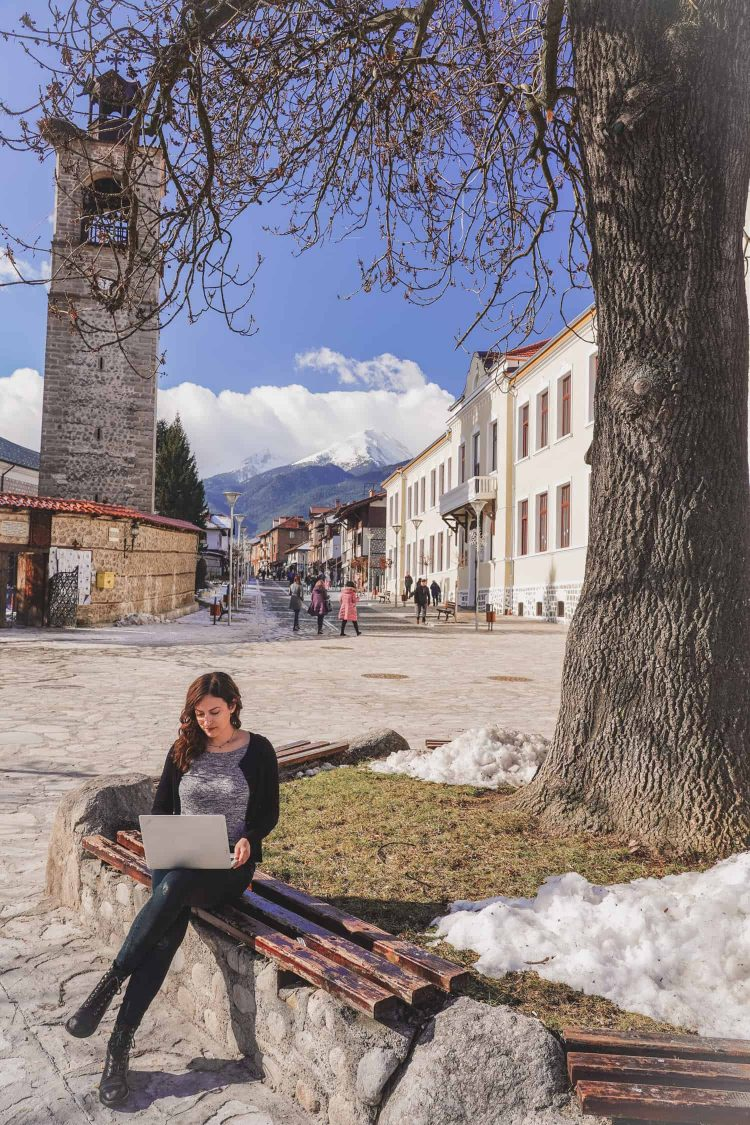 Kelsey, a digital nomad, working on her laptop outside under a tree in Bansko, Bulgaria