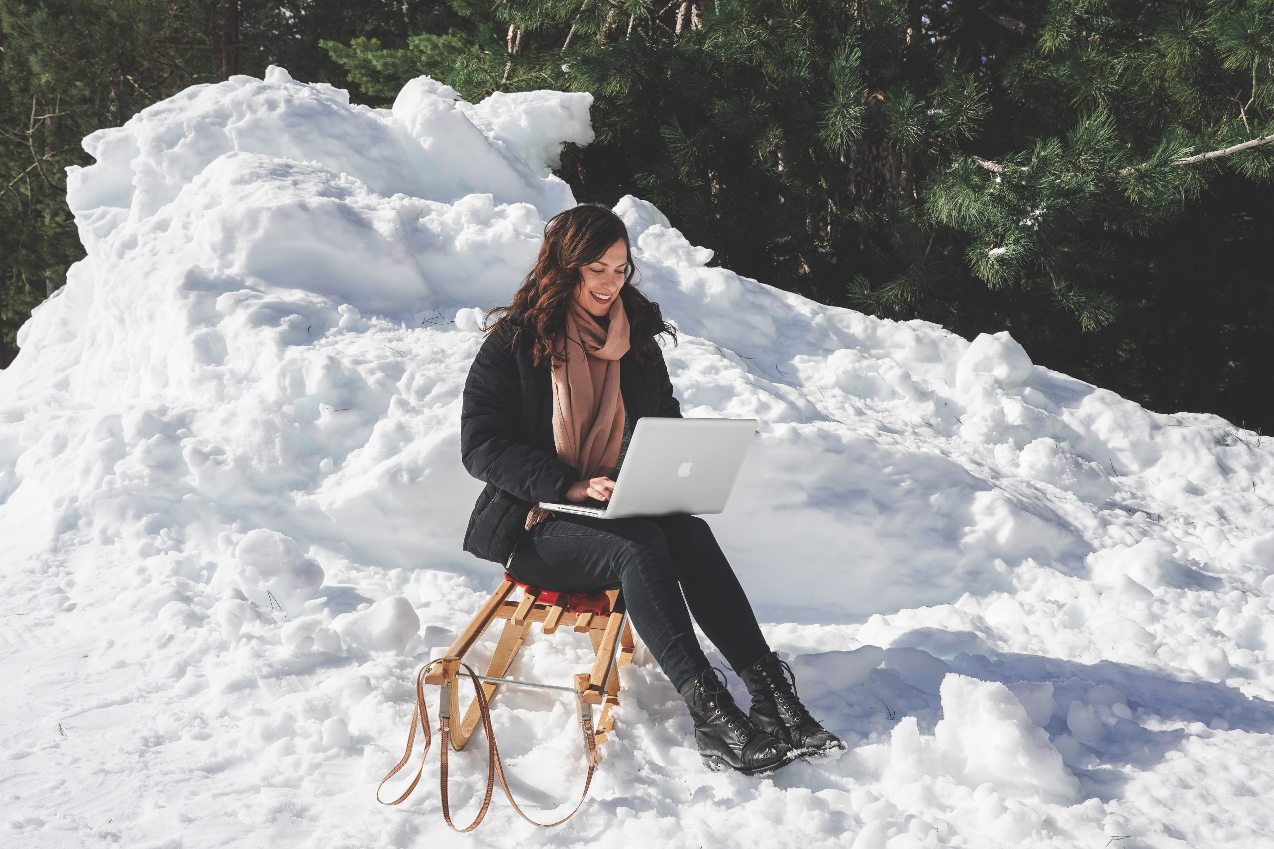 Kelsey, a digital nomad, sitting on a chair with her laptop in the snow in Bansko, Bulgaria