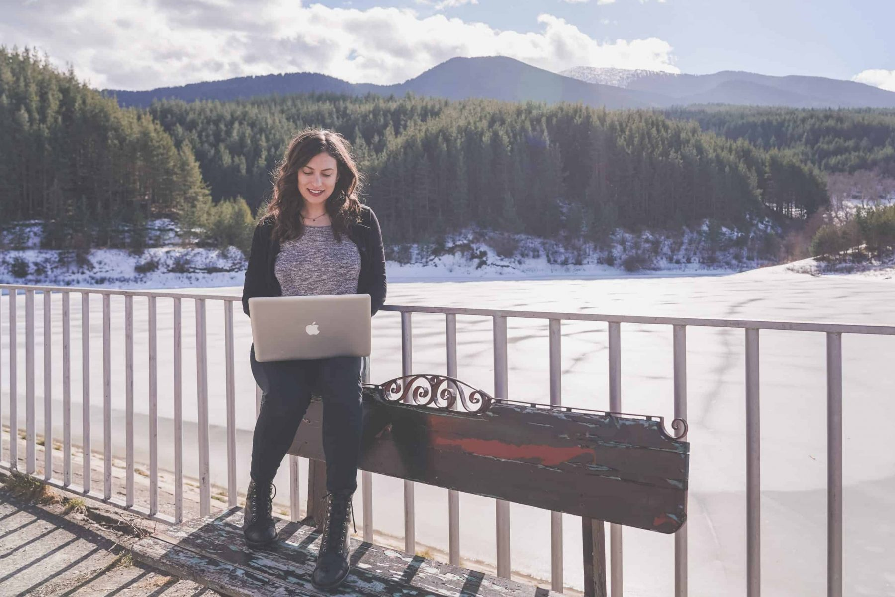 Digital nomad girl sitting on a bench with a computer above a lake surrounded by mountains