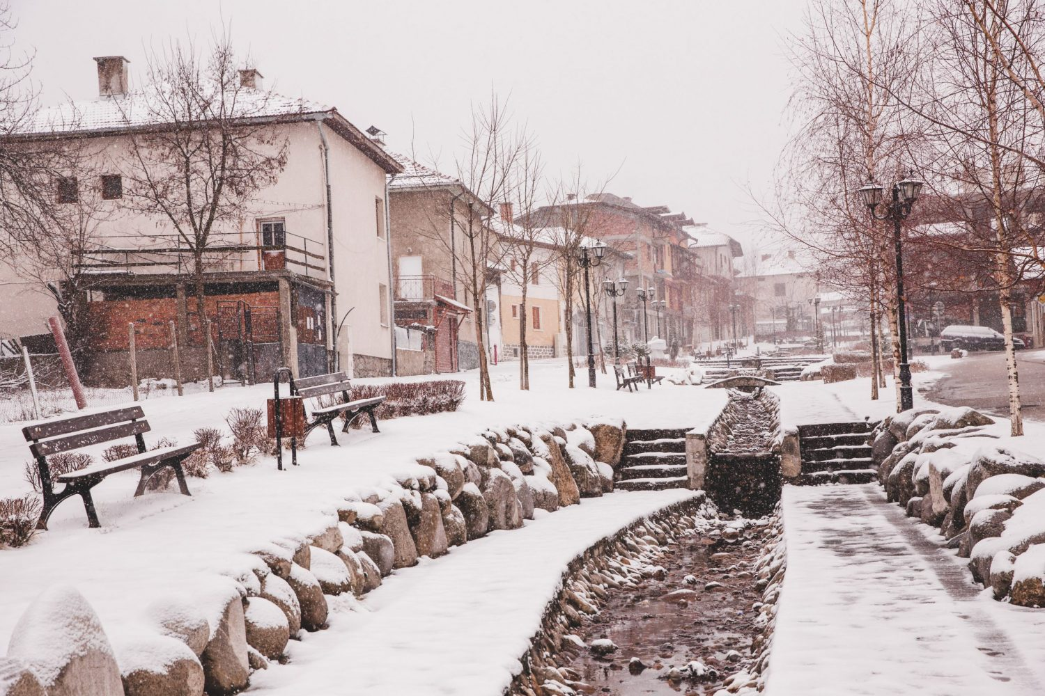 "The street ul ""Gotse Delchev"" in Bansko, Bulgaria has a river running through it and beautiful houses"