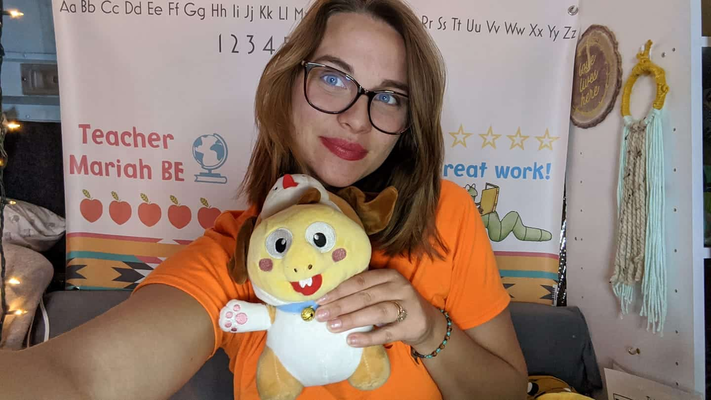 Online English teacher wearing an orange shirt and holding a yellow Dino doll with a simple background