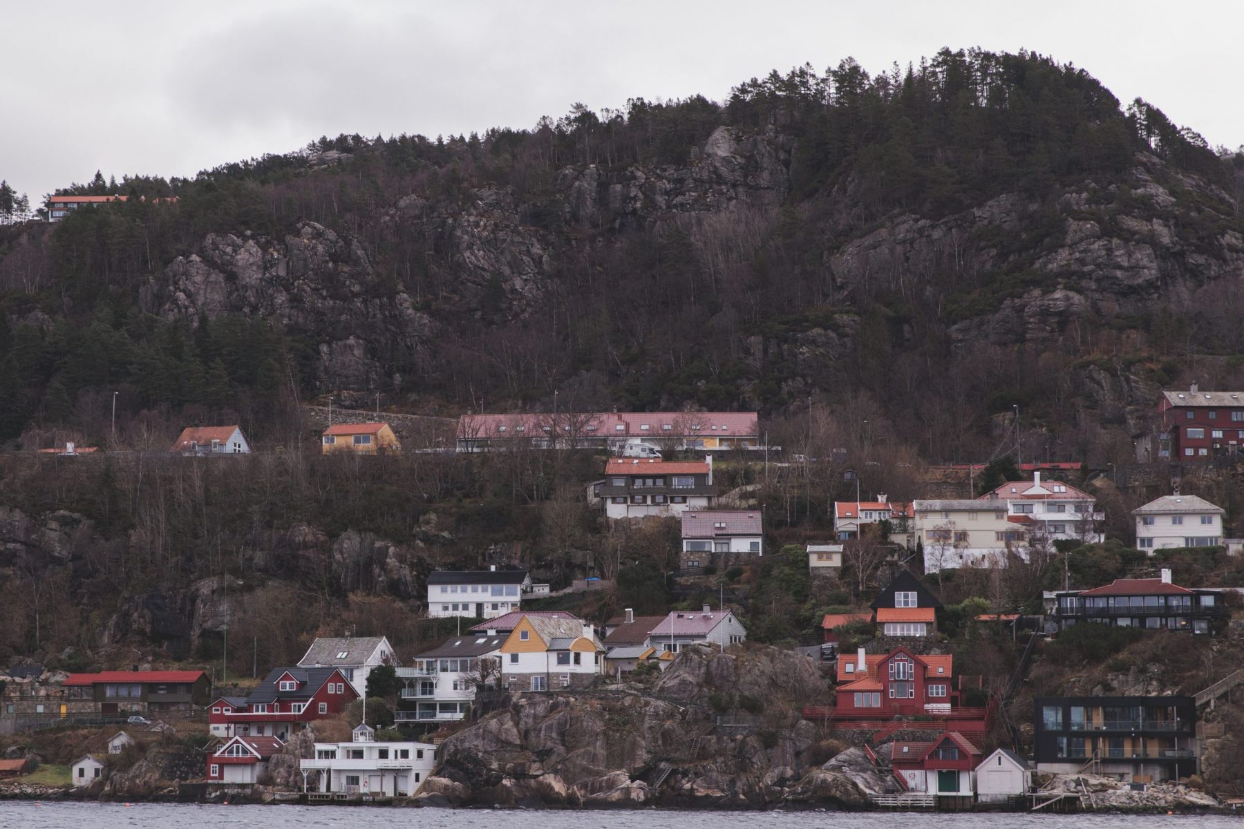 View of mountains and houses on the shore on a fjord tour in the Osterfjord from Bergen, Norway