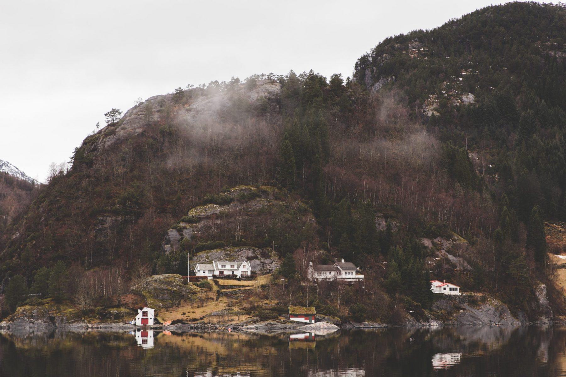 View of mountains, small white houses, fog, and water on a fjord tour in the Osterfjord from Bergen, Norway