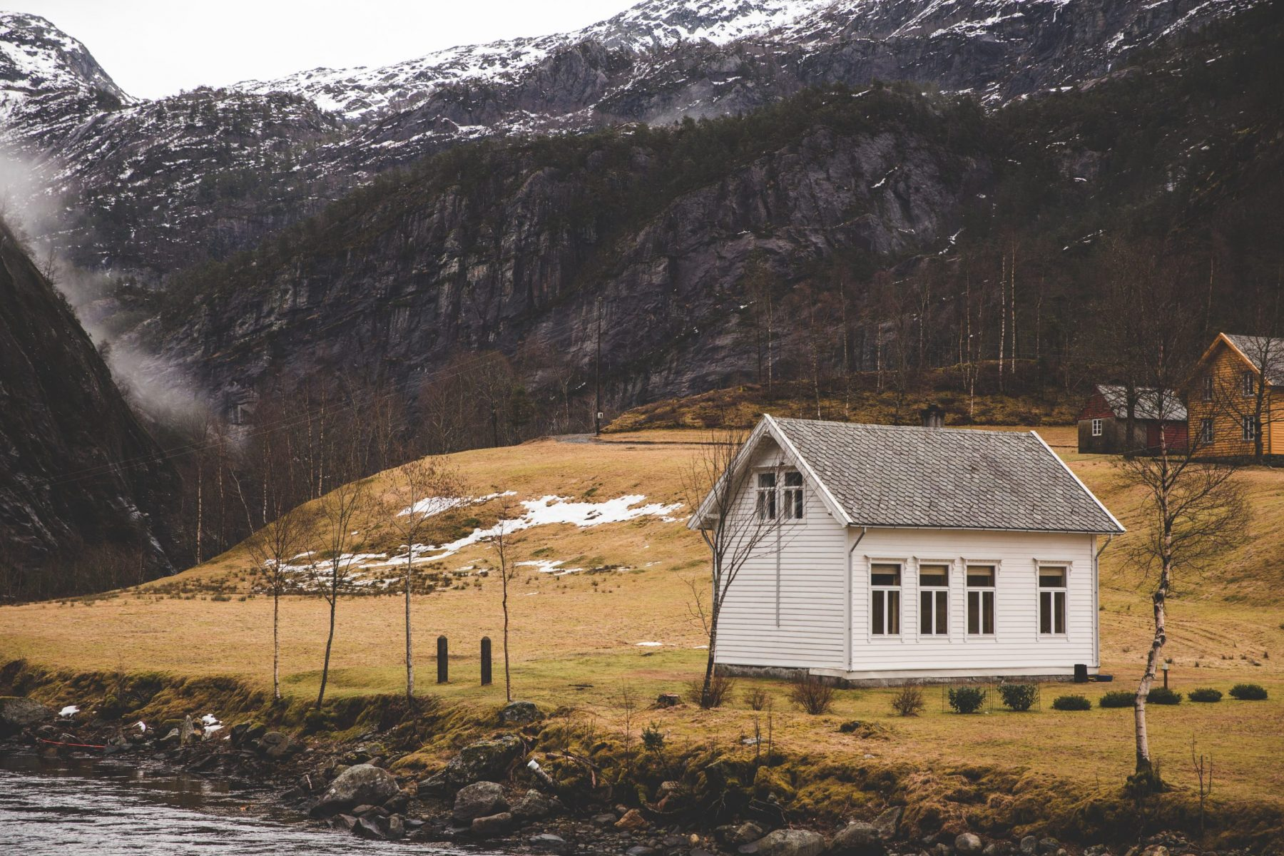 Pretty white house in nature surrounded by mountains and fog on the fjord cruise in Bergen, Norway