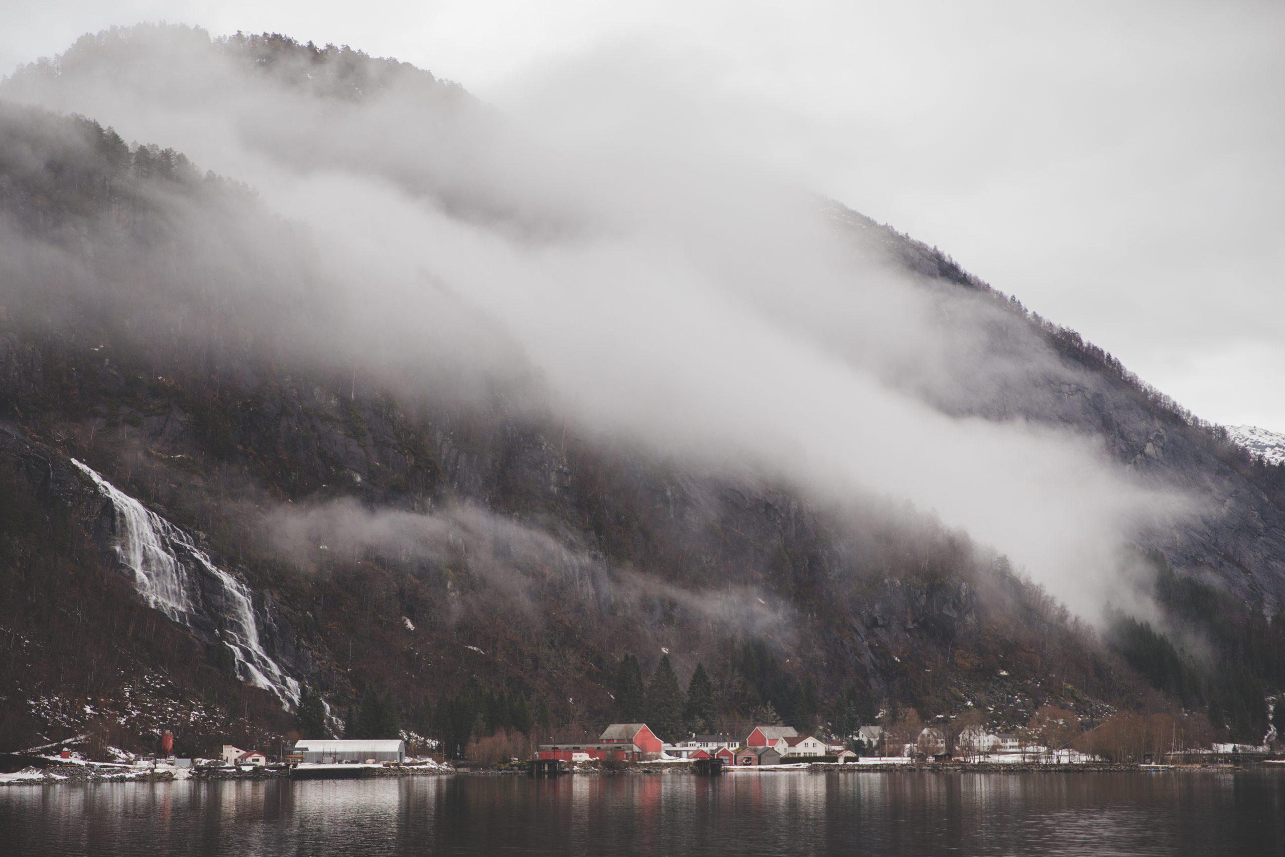 View of houses from the Rødne Fjord Cruise Boat with mountains and fog in the background