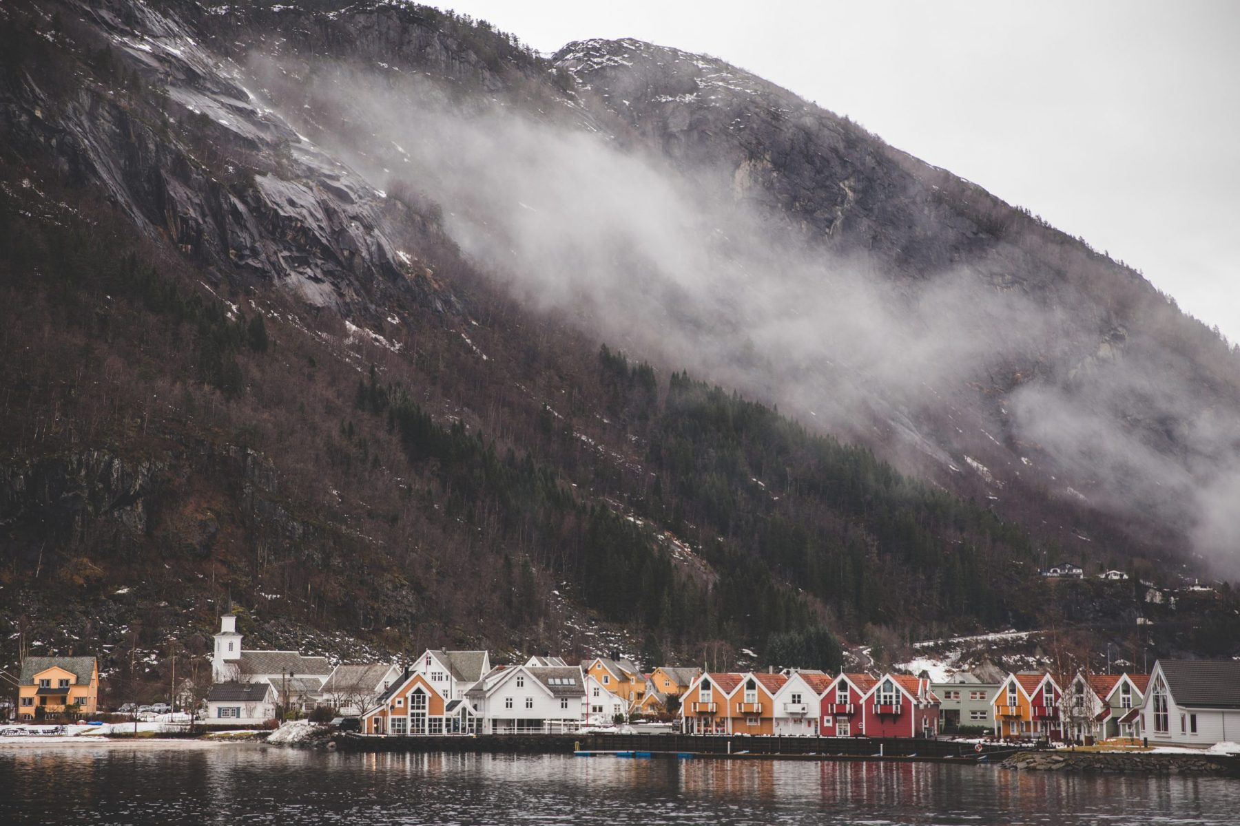 View of the village of Mo and its white, yellow, and red houses from the Rødne Fjord Cruise Boat with mountains and fog in the background