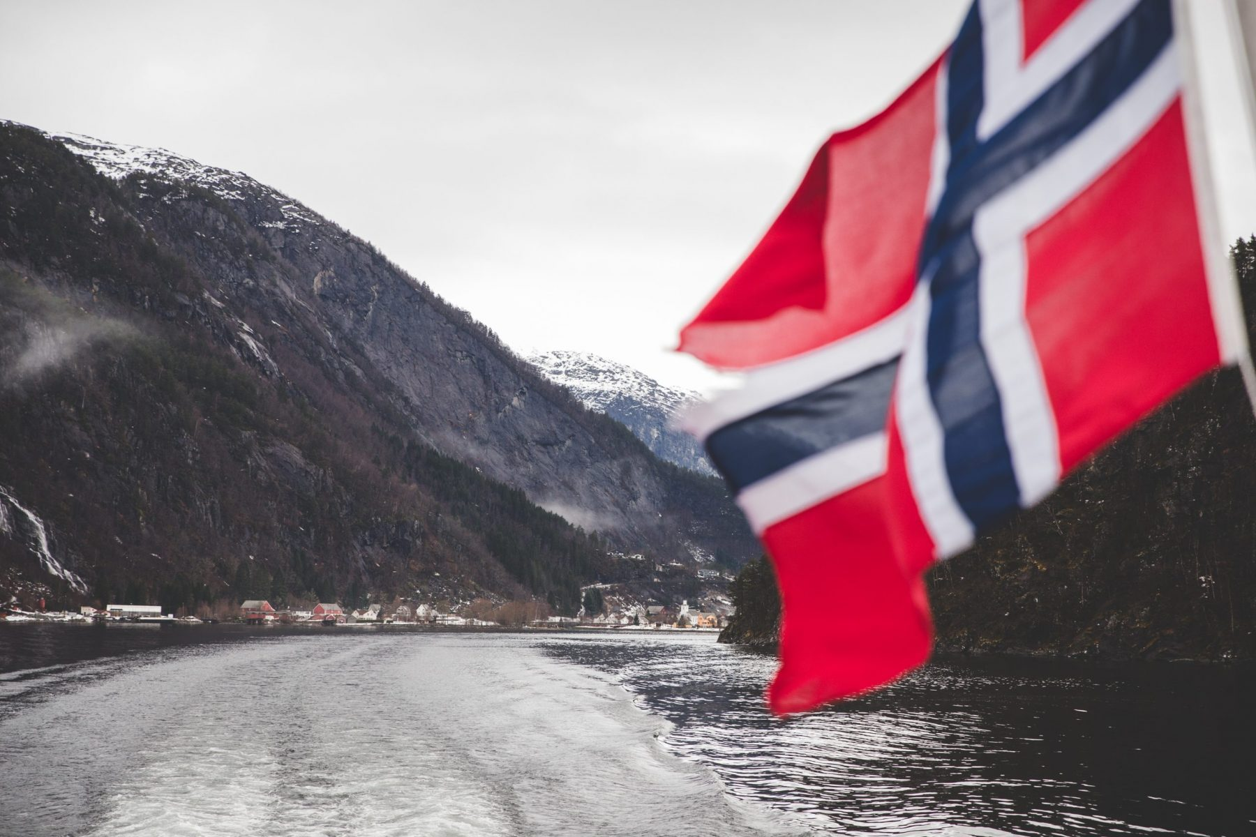 Norwegian Flag Waving on the Rødne Fjord Cruise Tour Boat with mountains in the background