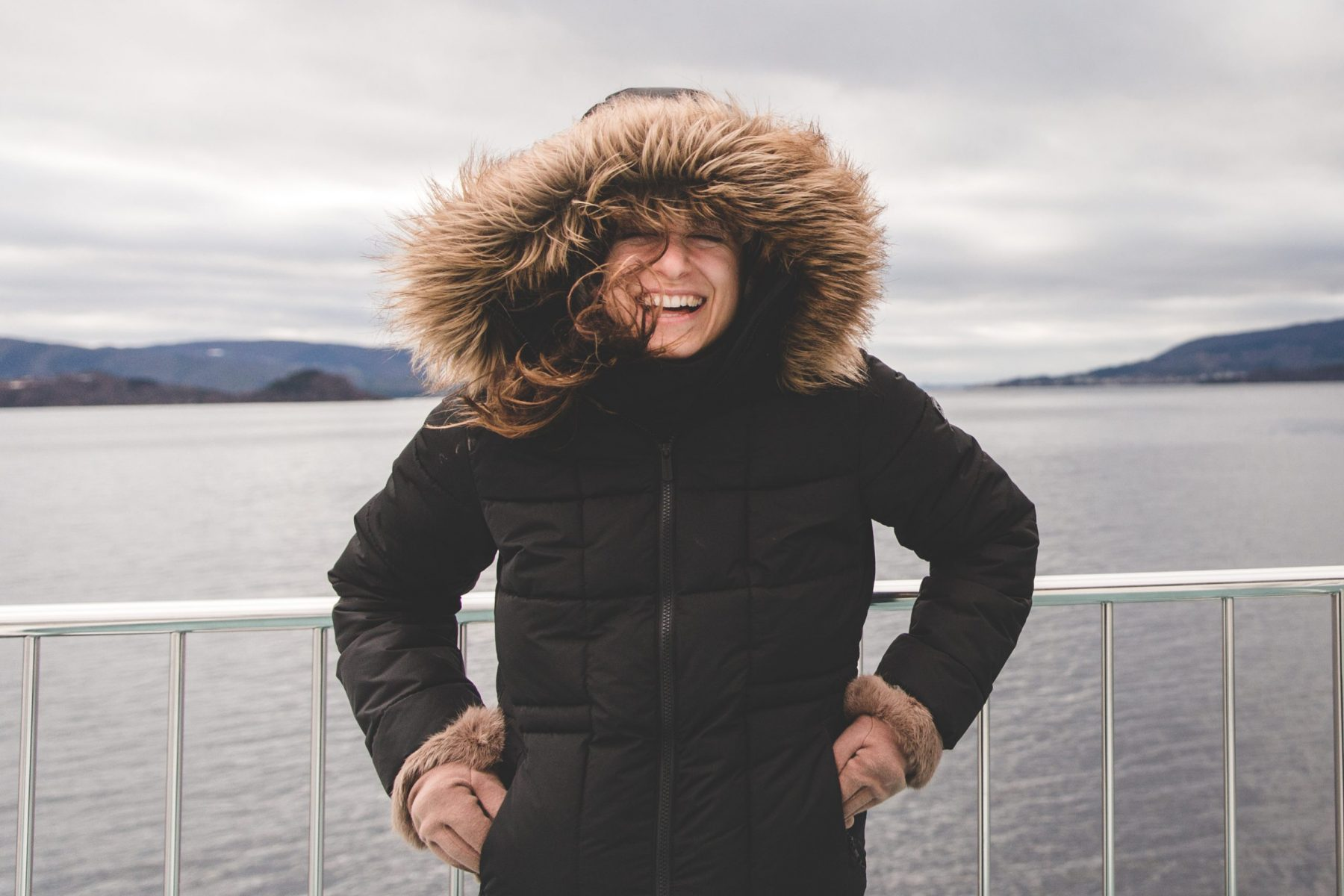 Kelsey is wearing a winter coat with a fur hood and tan gloves while smiling wide during the Rødne Fjord Cruise on the Osterfjord from Bergen, Norway in the winter