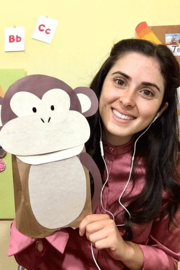 Traveling teacher holding a paper monkey in front of her VIP Kid classroom background