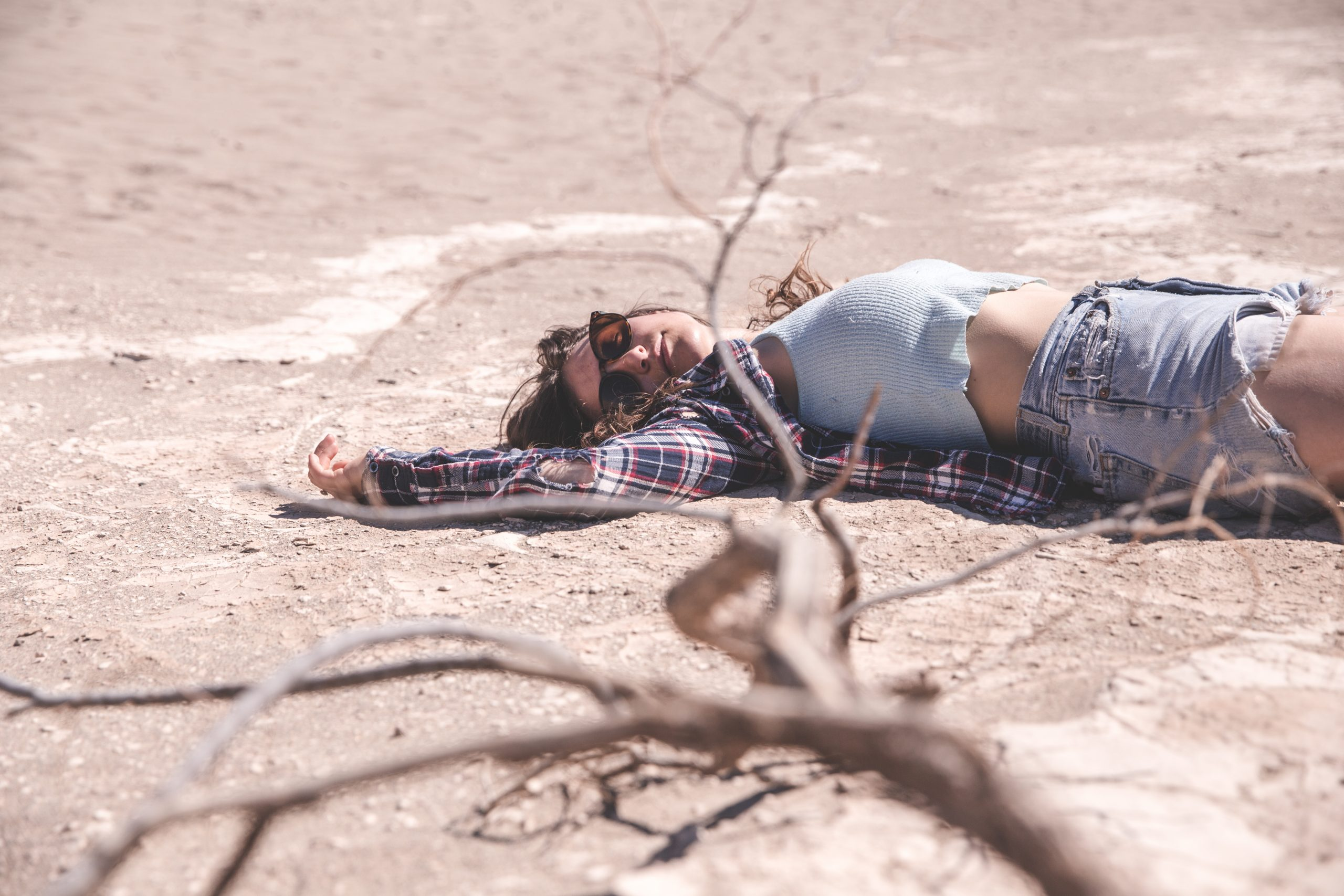 Kelsey laying on the ground in the desert of Death Valley National Park in California