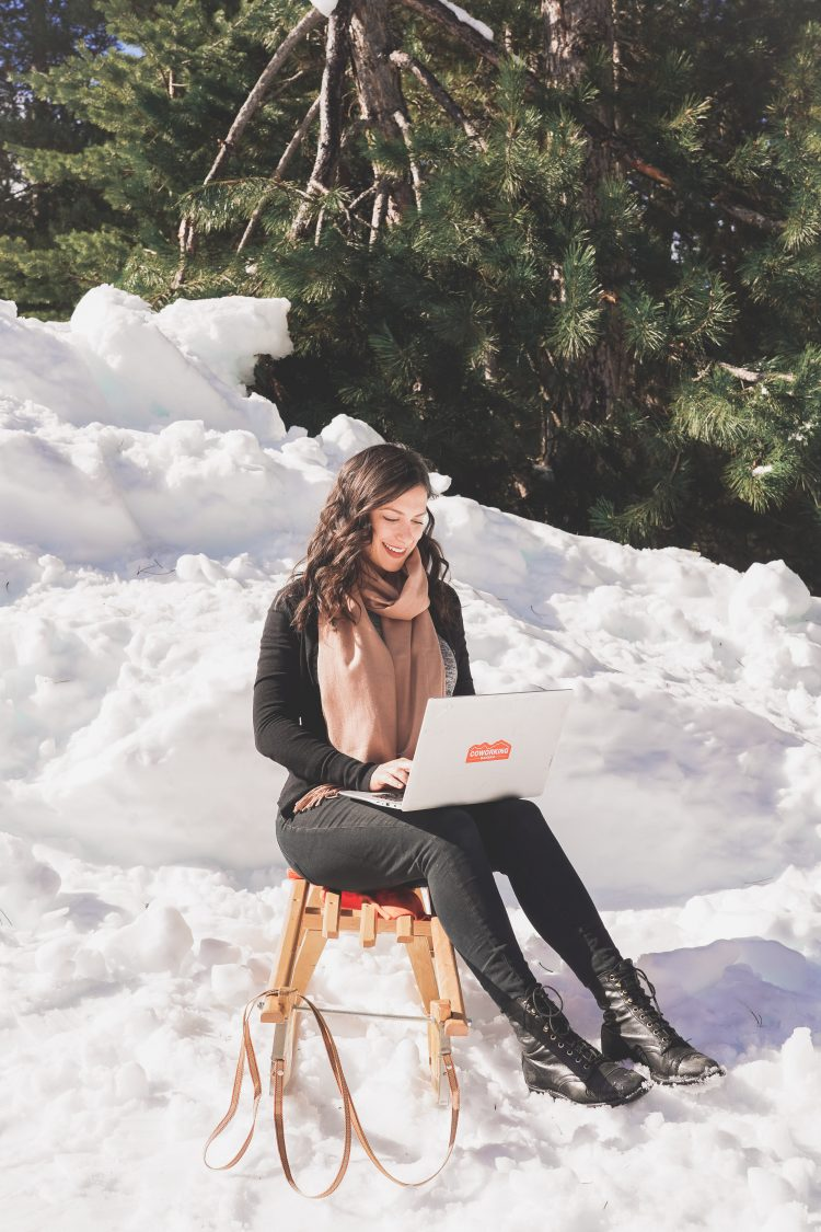 Kelsey sitting in the snow with a computer, living as a digital nomad in Bansko, Bulgaria