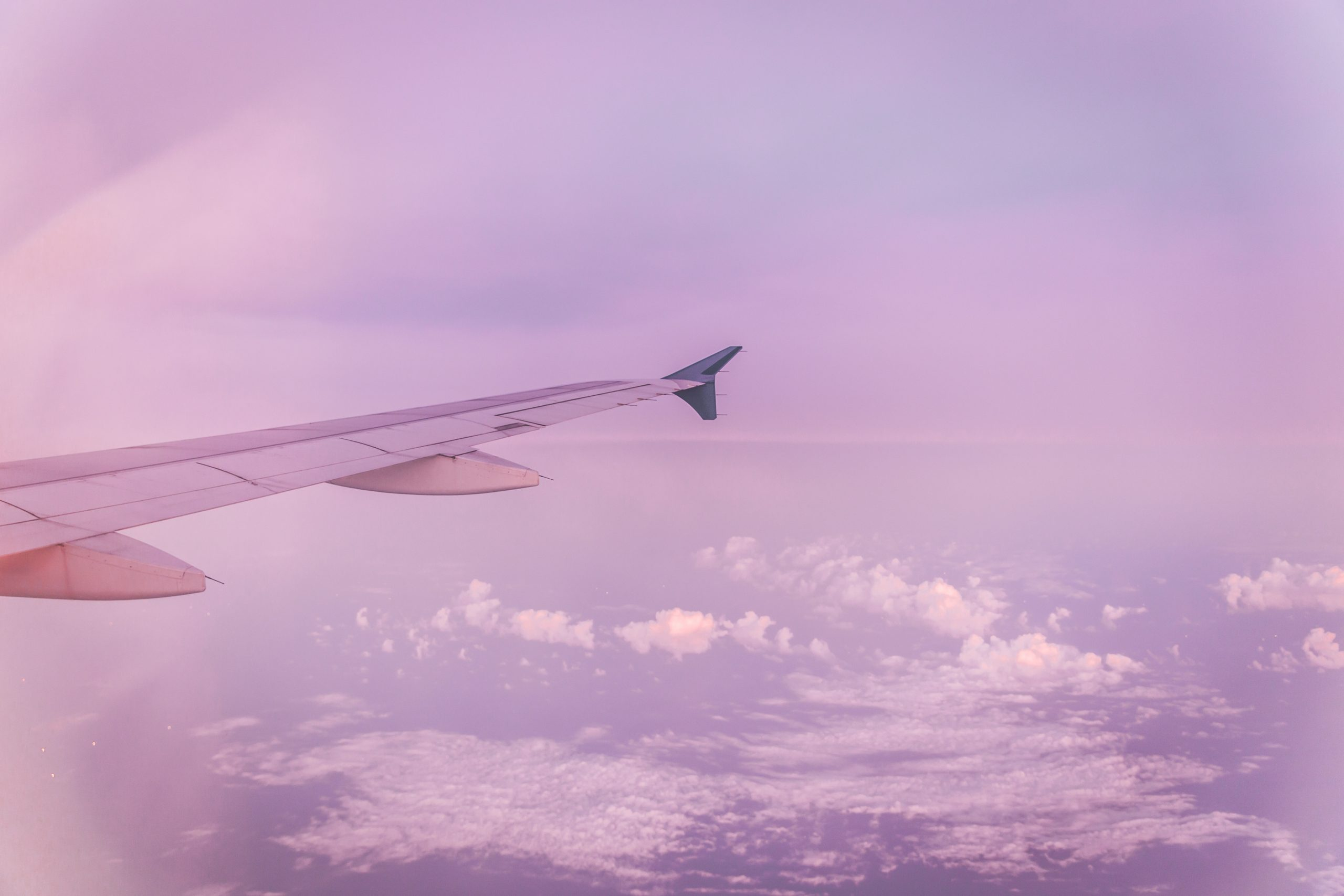 Plane wing surrounded by pink sky and clouds - the view from the plane's window