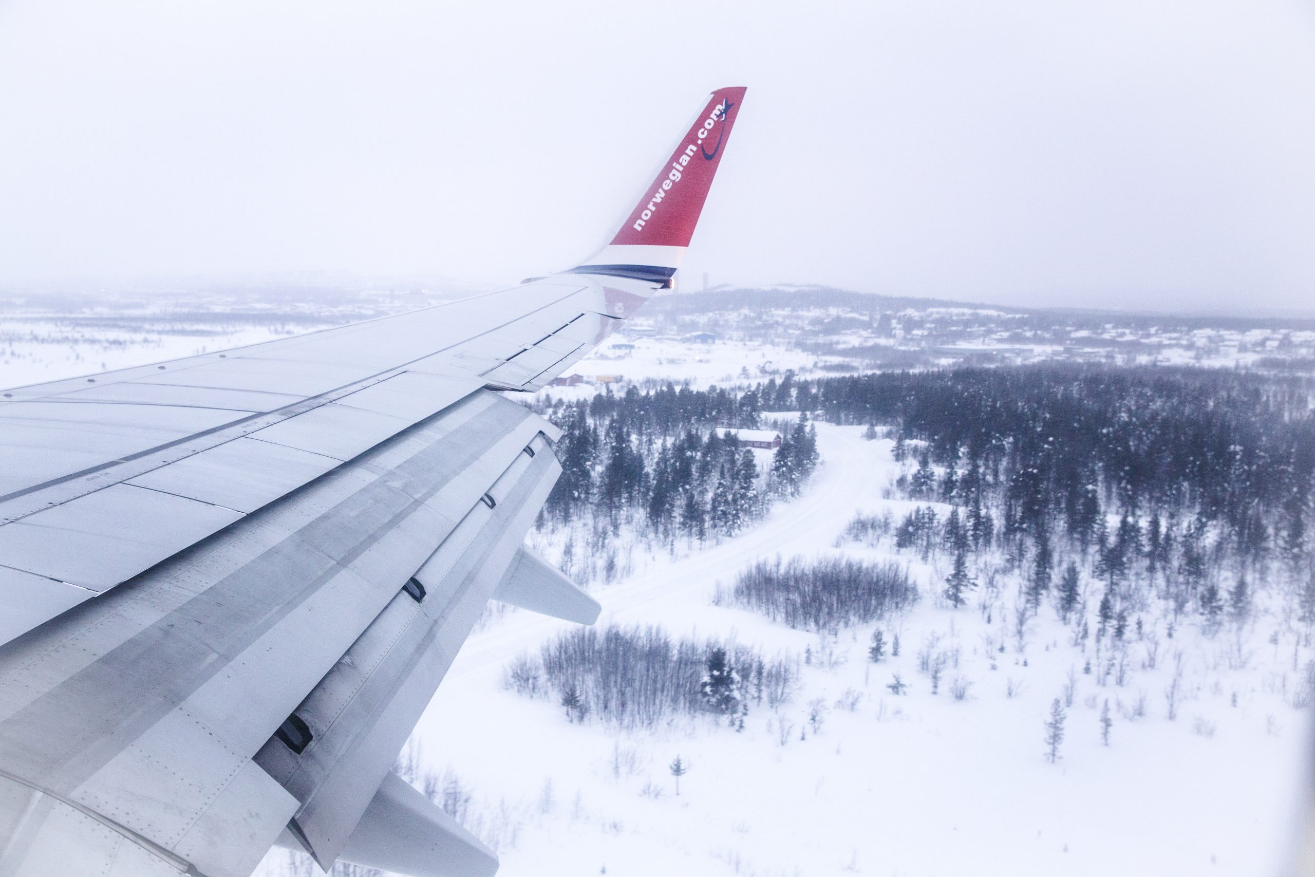 """View form airplane window, showing an airplane wing with """"Norwegian"""" written on it, overlooking a snowy landscape with trees in winter."""