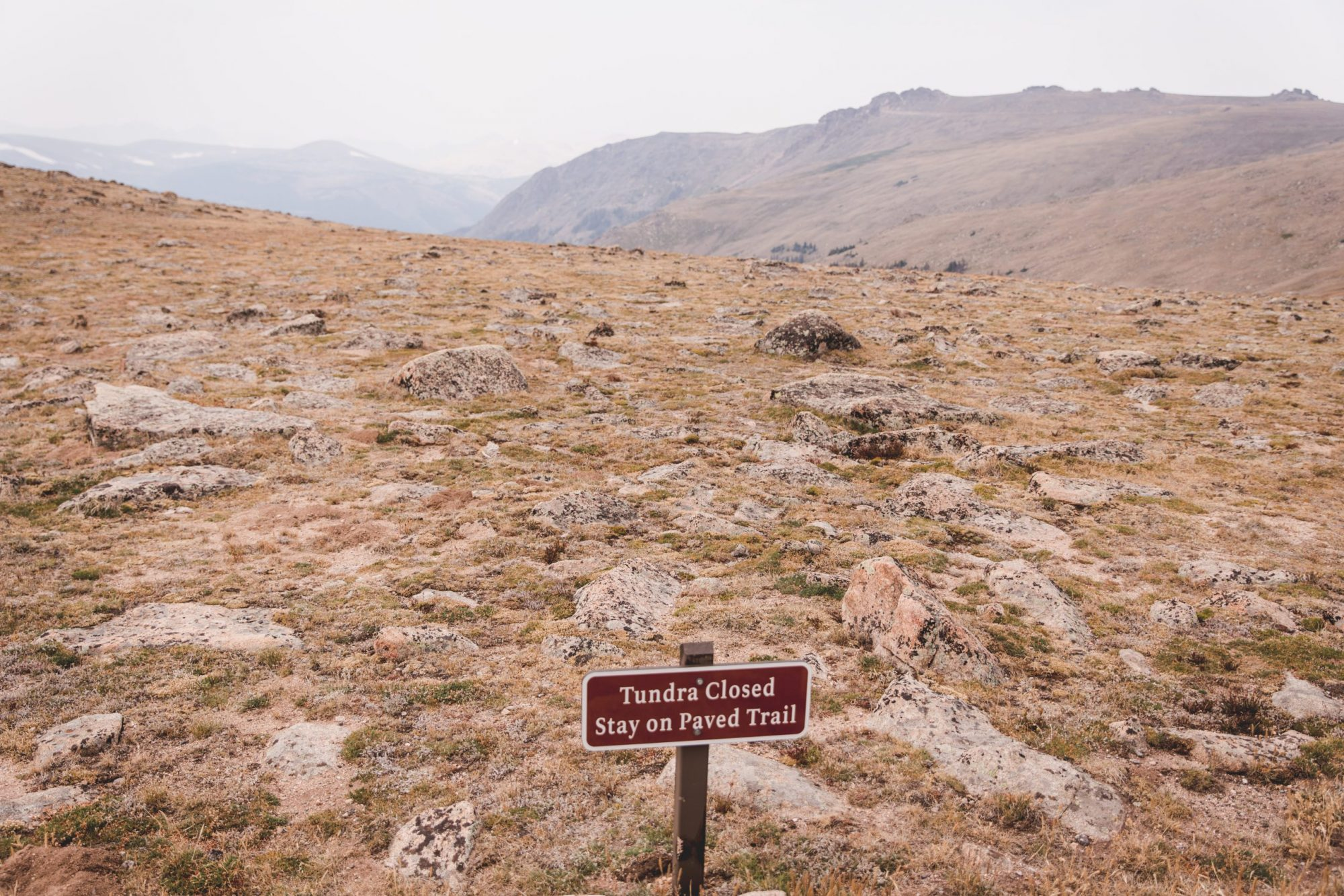 """""""Tundra Closed"""" Sign at Rocky Mountain National Park at the Forest Canyon Overlook with a view of the tundra, yellow grass, rocks, and mountains"""