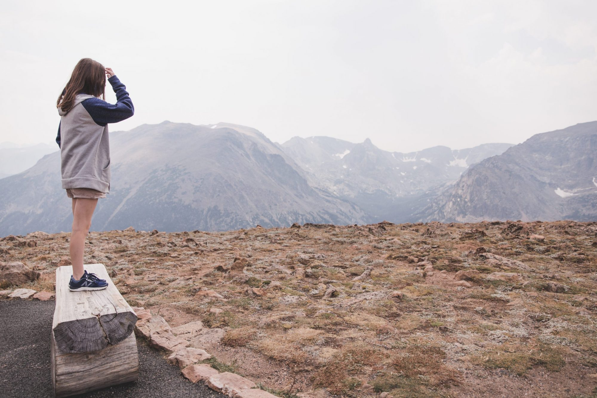 Girl standing at Forest Canyon Overlook at Rocky Mountain National Park with a view of the tundra and mountains