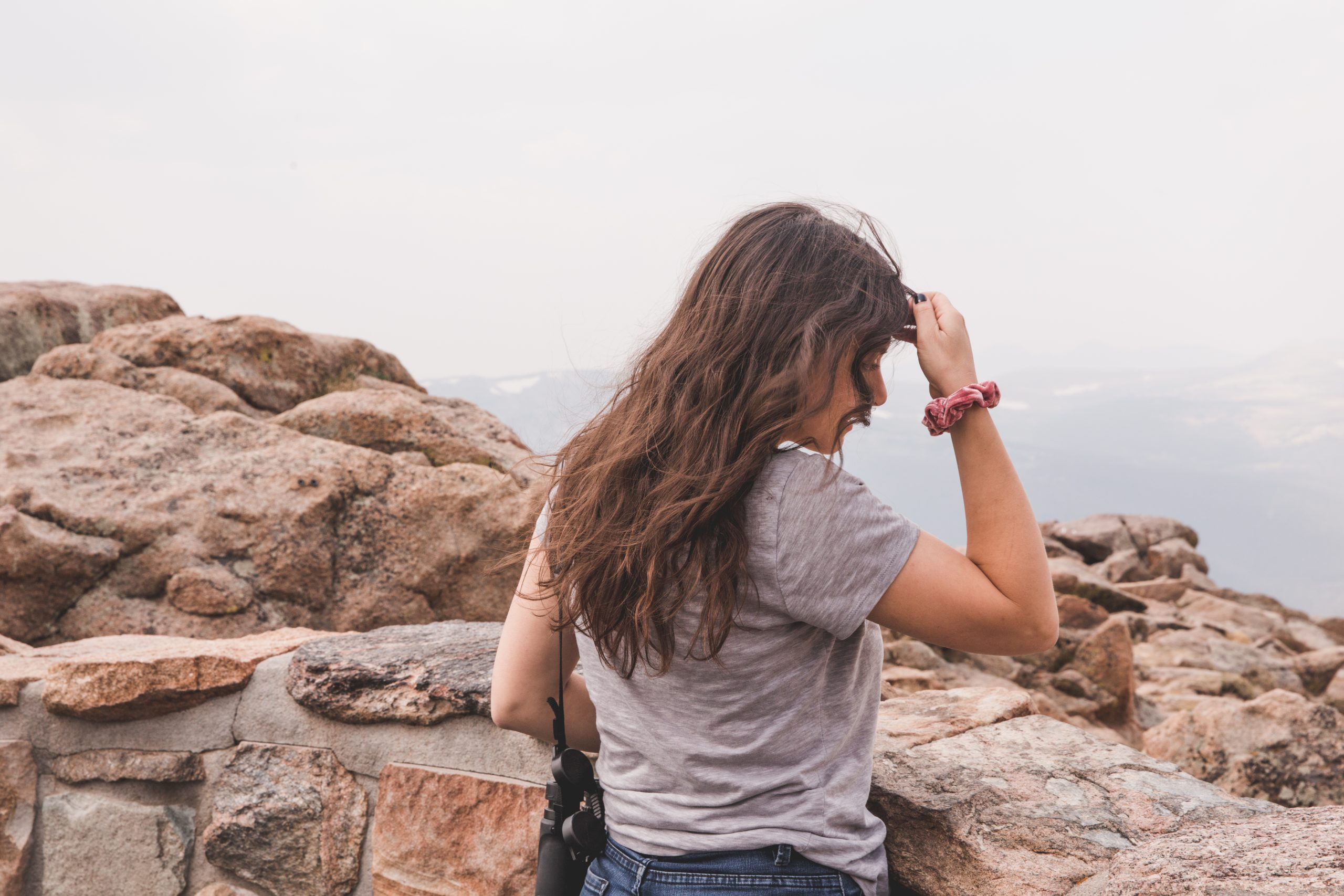 Kelsey standing with her back to the camera, touching her hair with a pink scrunchie on her wrist. She looks out at the mountains in Rocky Mountain National Park in Colorado.