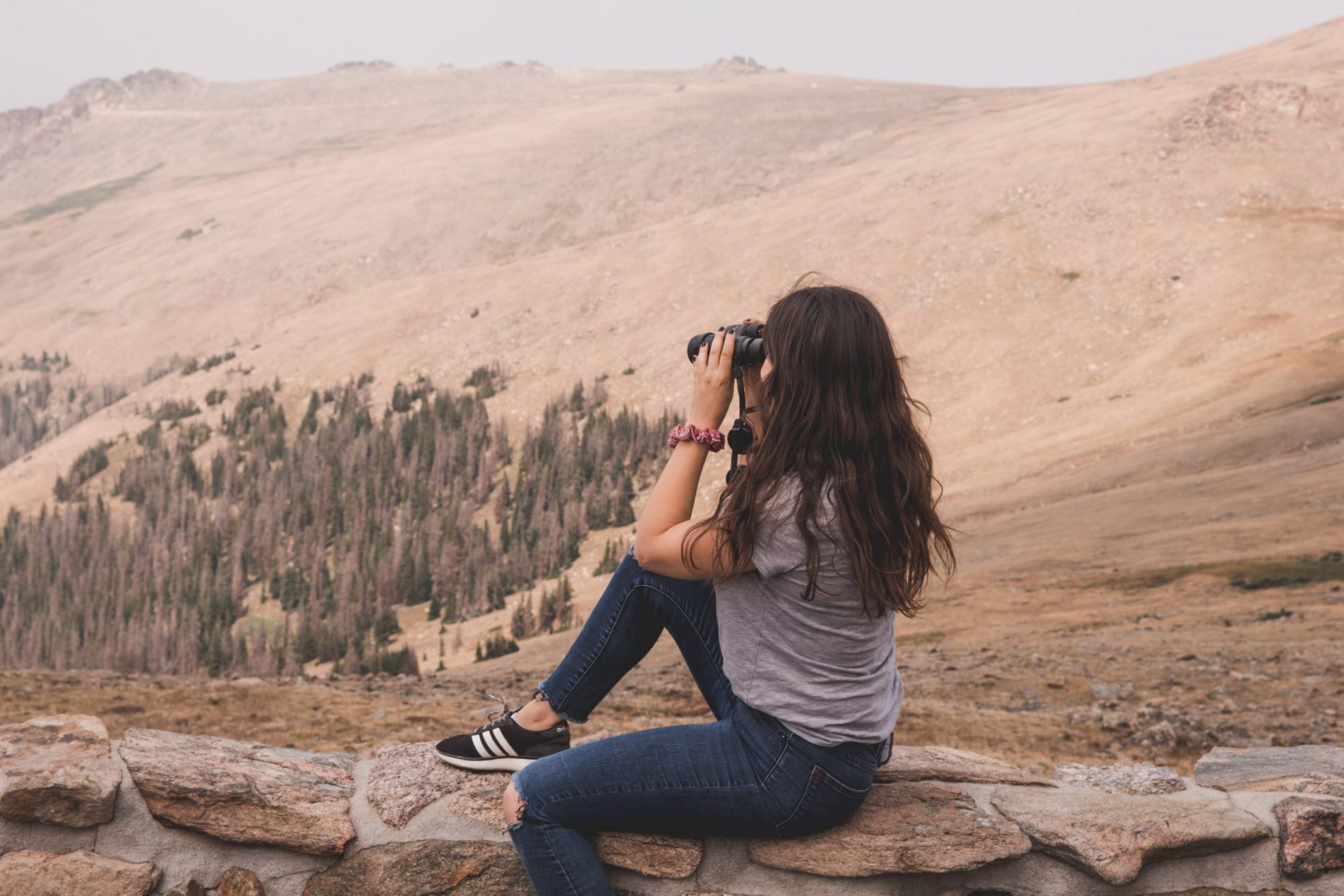 Kelsey looking at the tundra, pine trees, and mountains with binoculars at the Forest Canyon Overlook at Rocky Mountain National Park