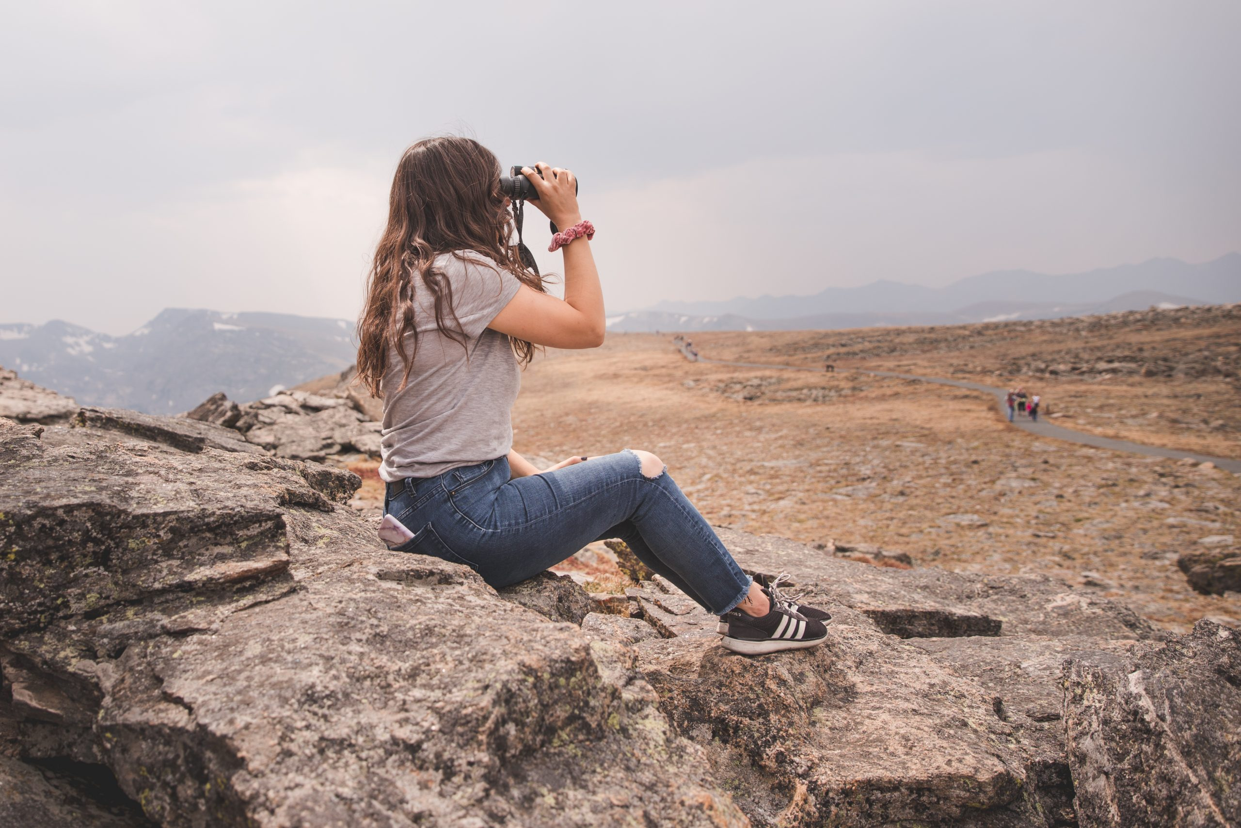 Kelsey looking for animals with binoculars at Rocky Mountain National Park in Colorado. Kelsey is sitting on a rock and holding the binoculars up to her eyes, and is surrounded by tundra habitat containing rocky terrain and short golden grass.