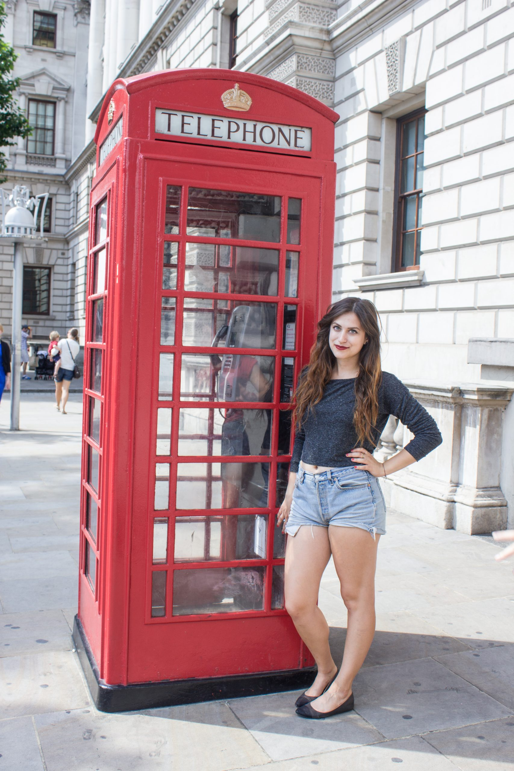 Kelsey standing at a red telephone booth in London
