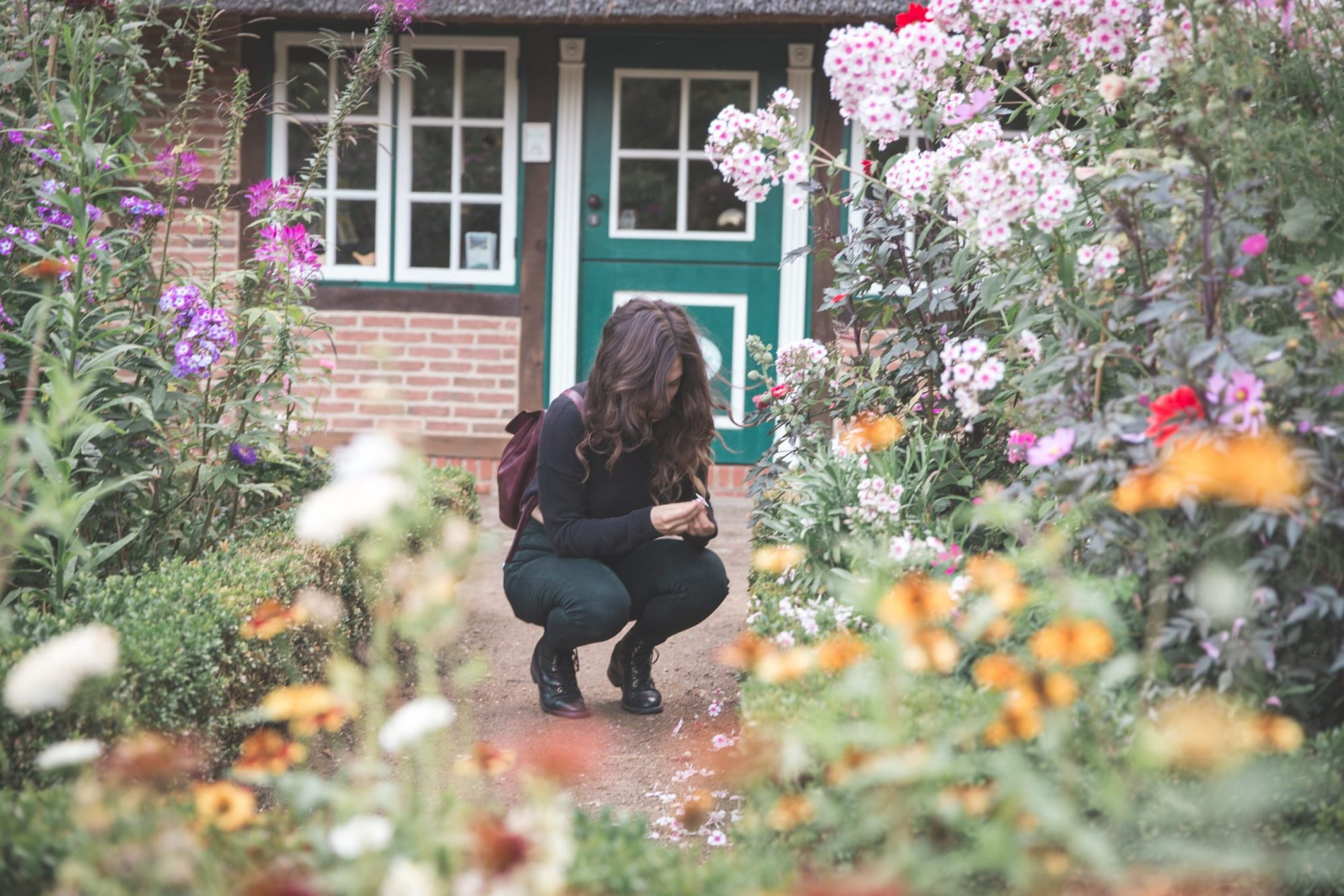 Kelsey bending down and wearing new boots while looking at a flower in the The Loki Schmidt Botanical Gardens in Hamburg, Germany