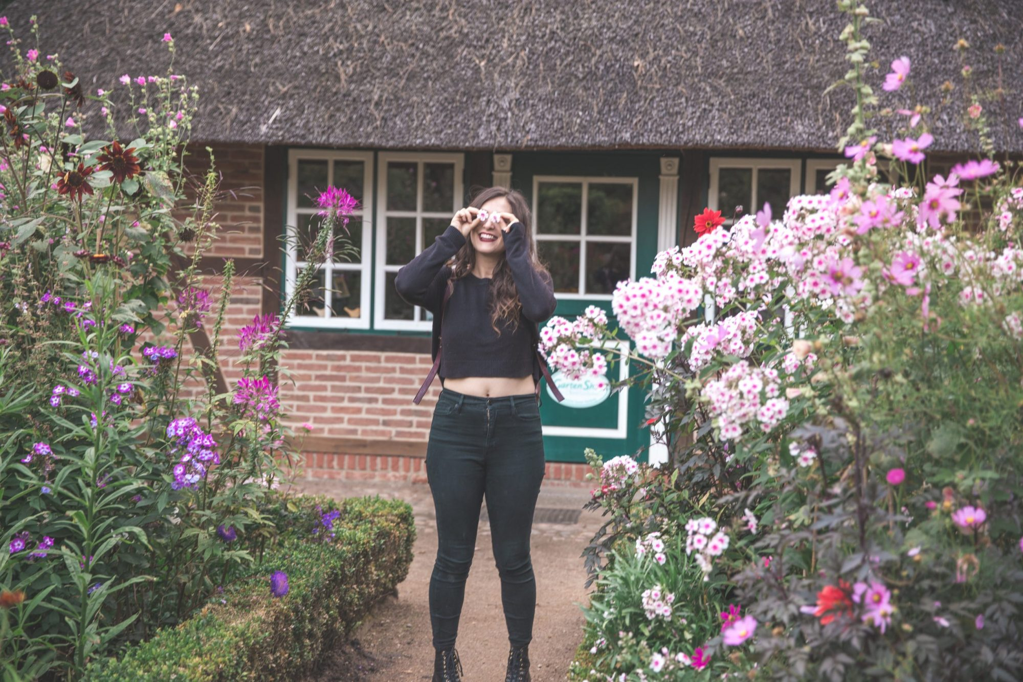 Kelsey holding flowers up to her eyes in front of a brick building surrounded by flowers in The Loki Schmidt Botanical Gardens in Hamburg, Germany