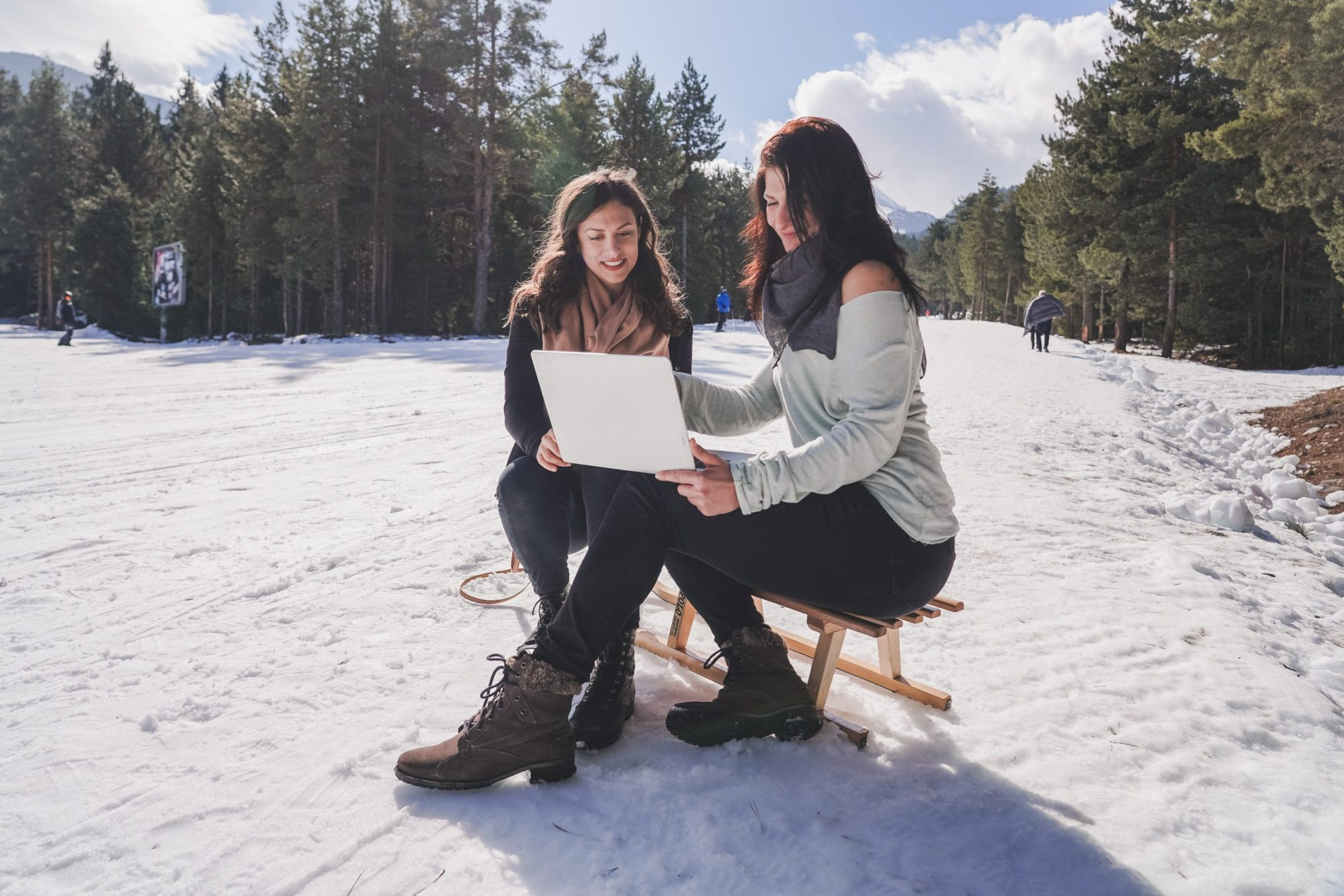 2 digital nomad girls sitting on the computer in the snow