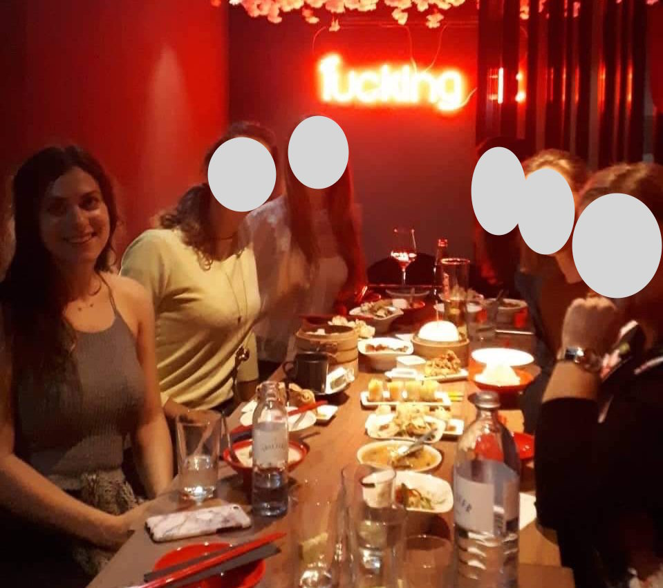 6 girls at dinner together in a red restaurant with food on the table