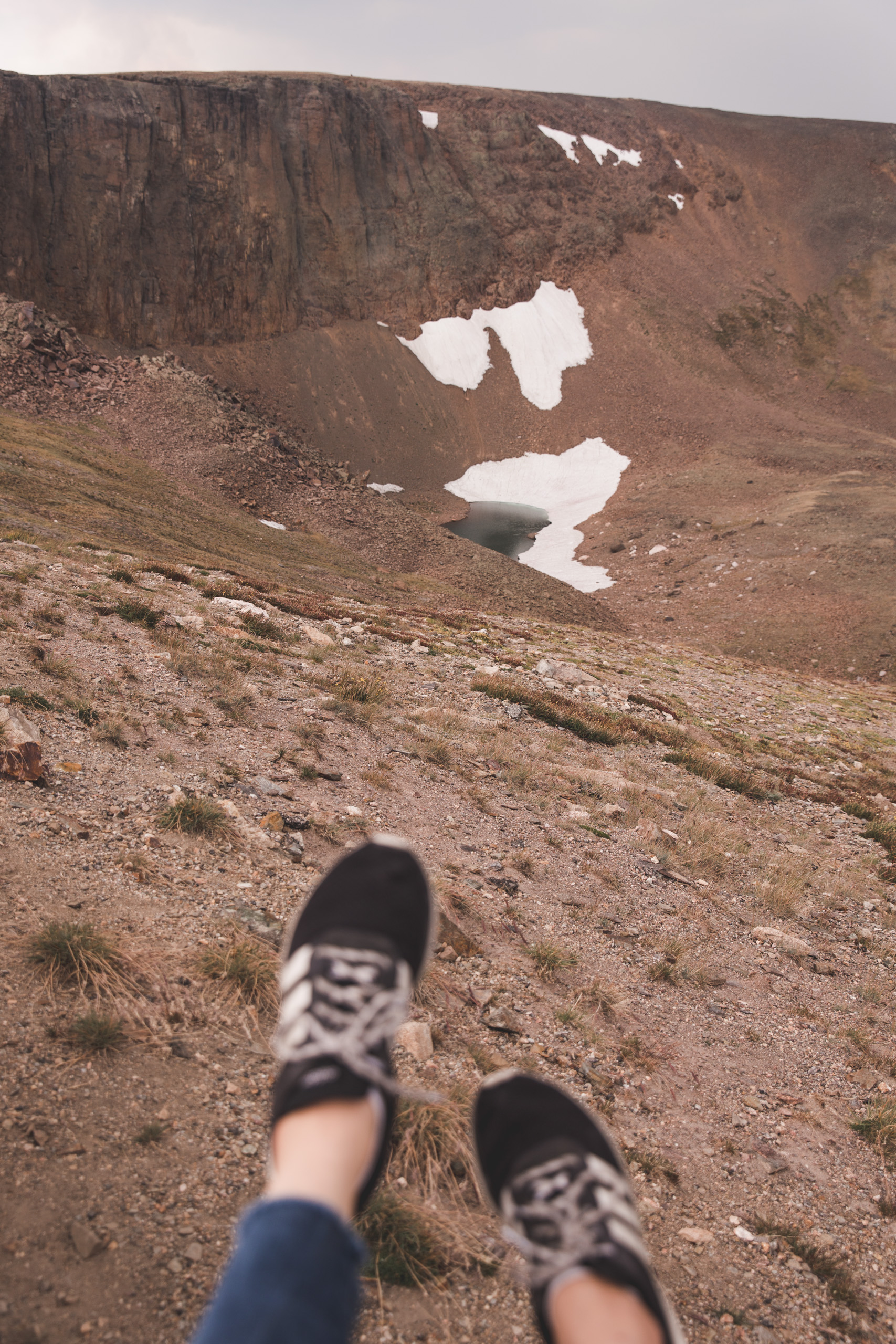 Kelsey's shoes with Lava Cliffs in Rocky Mountain National Park in the background. There's a little bit of snow on the mountains in the background, overlooking a blue lake.