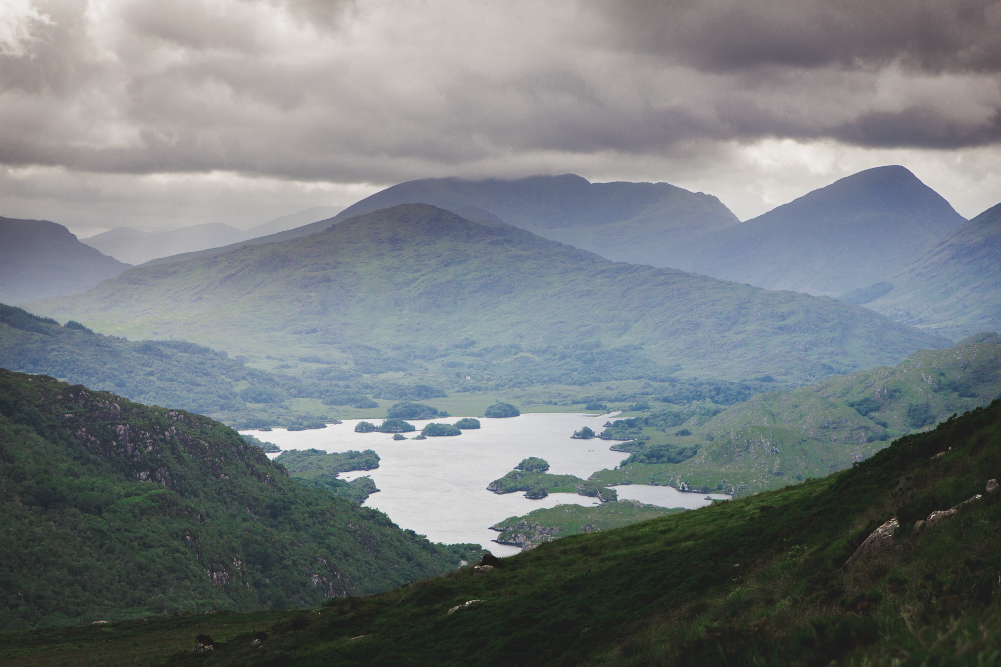 Rainy and cloudy view from the top of Torc Mountain in Killarney National Park in Ireland of other mountains and a lake in the distance