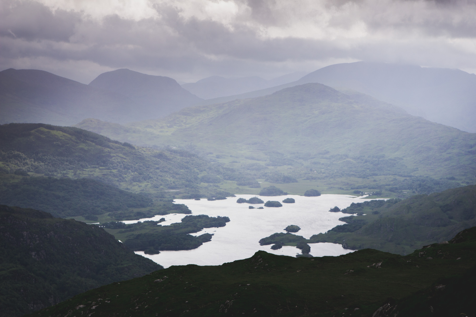 View of a lake, mountains, hills, and grass from the top of Torc Mountain in Killarney National Park in Ireland