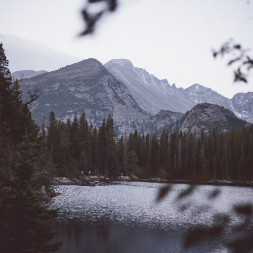 Bear Lake at dusk in Rocky Mountain National Park in Colorado surrounded by trees and mountains