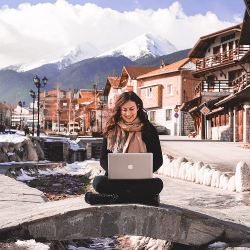 Kelsey, a Digital Nomad, sits on a stone bridge in front of houses and mountains in Bansko, Bulgaria