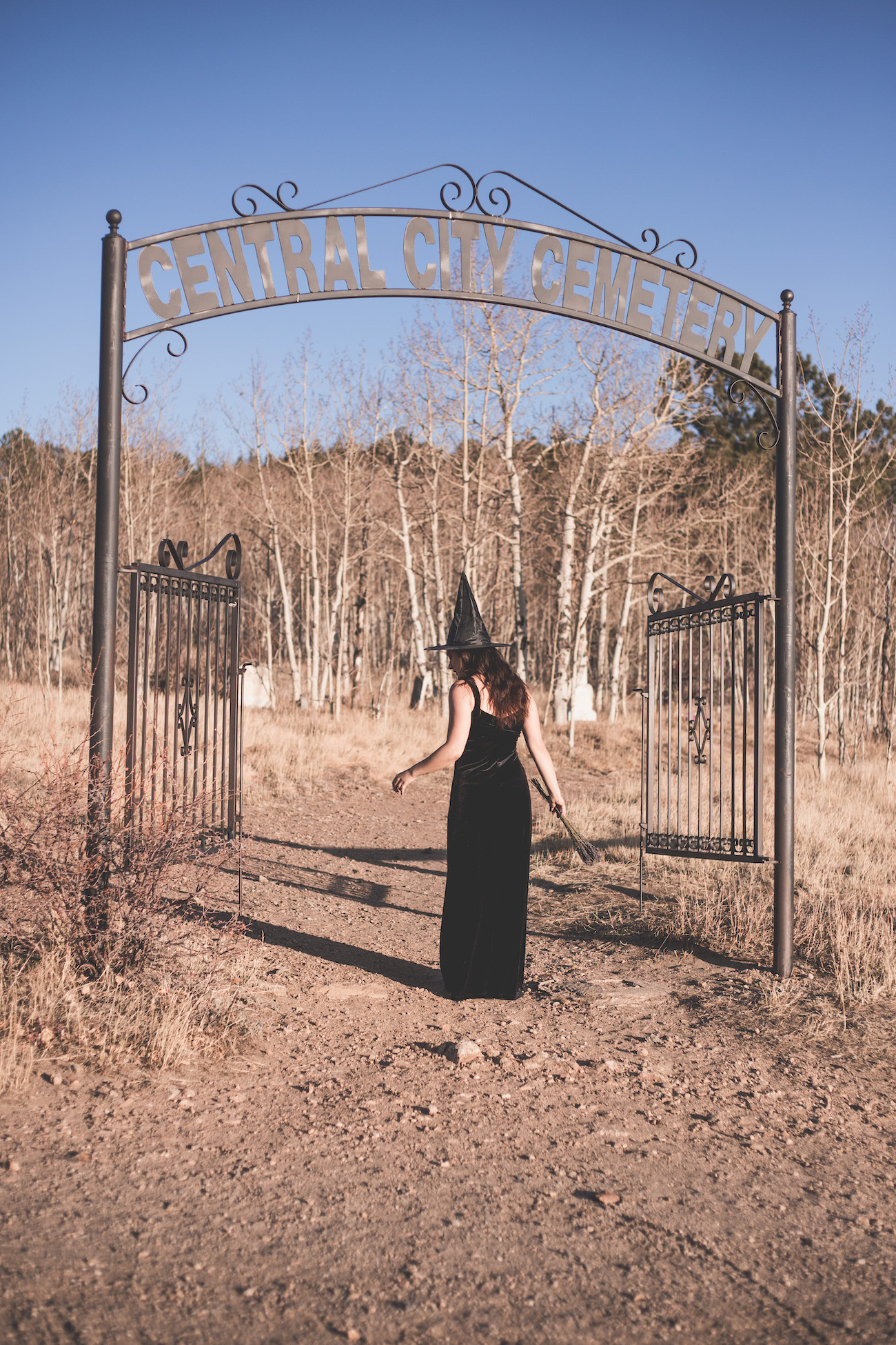 """Kelsey dressed in a long black dress with a witch's hat, walking into the Central City Cemetery in Colorado. The wrought iron gates have a sign above that says """"Central City Cemetery""""."""