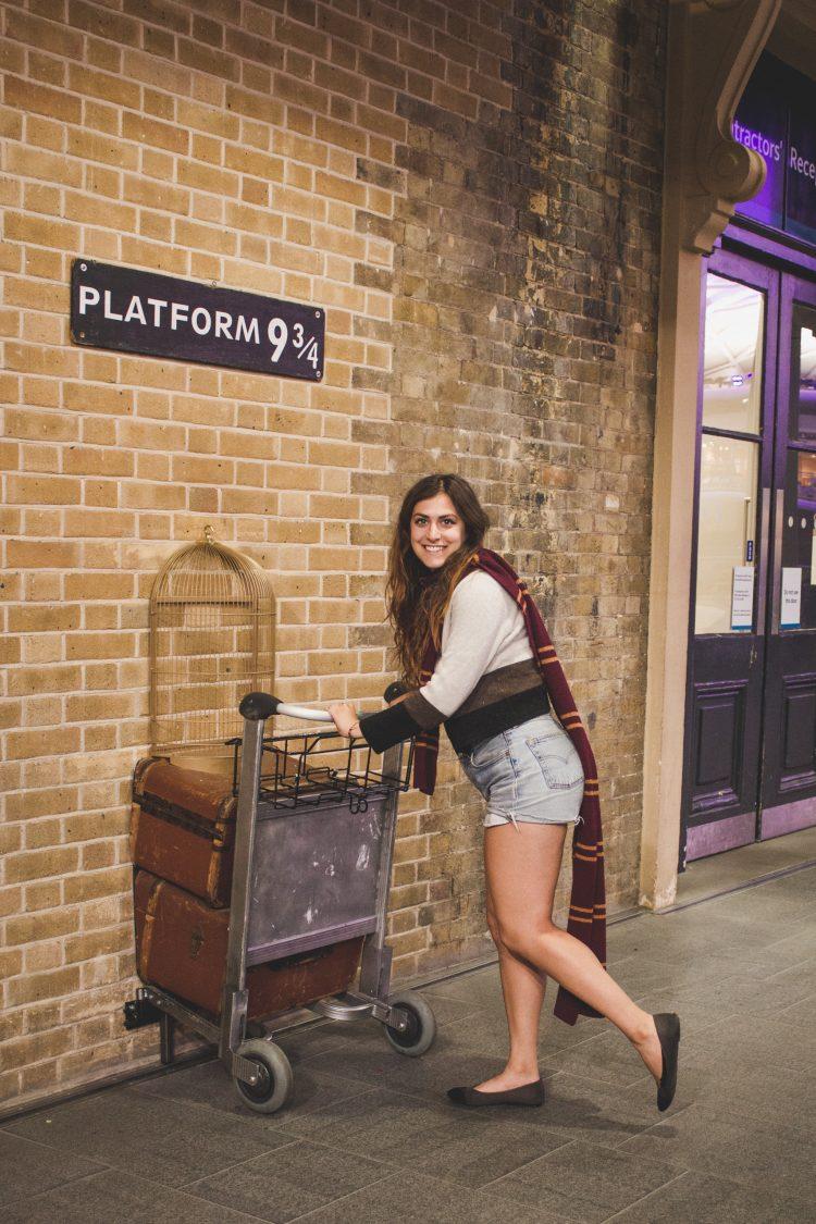 Kelsey standing at Platform 9 3/4 at King's Cross Station in London